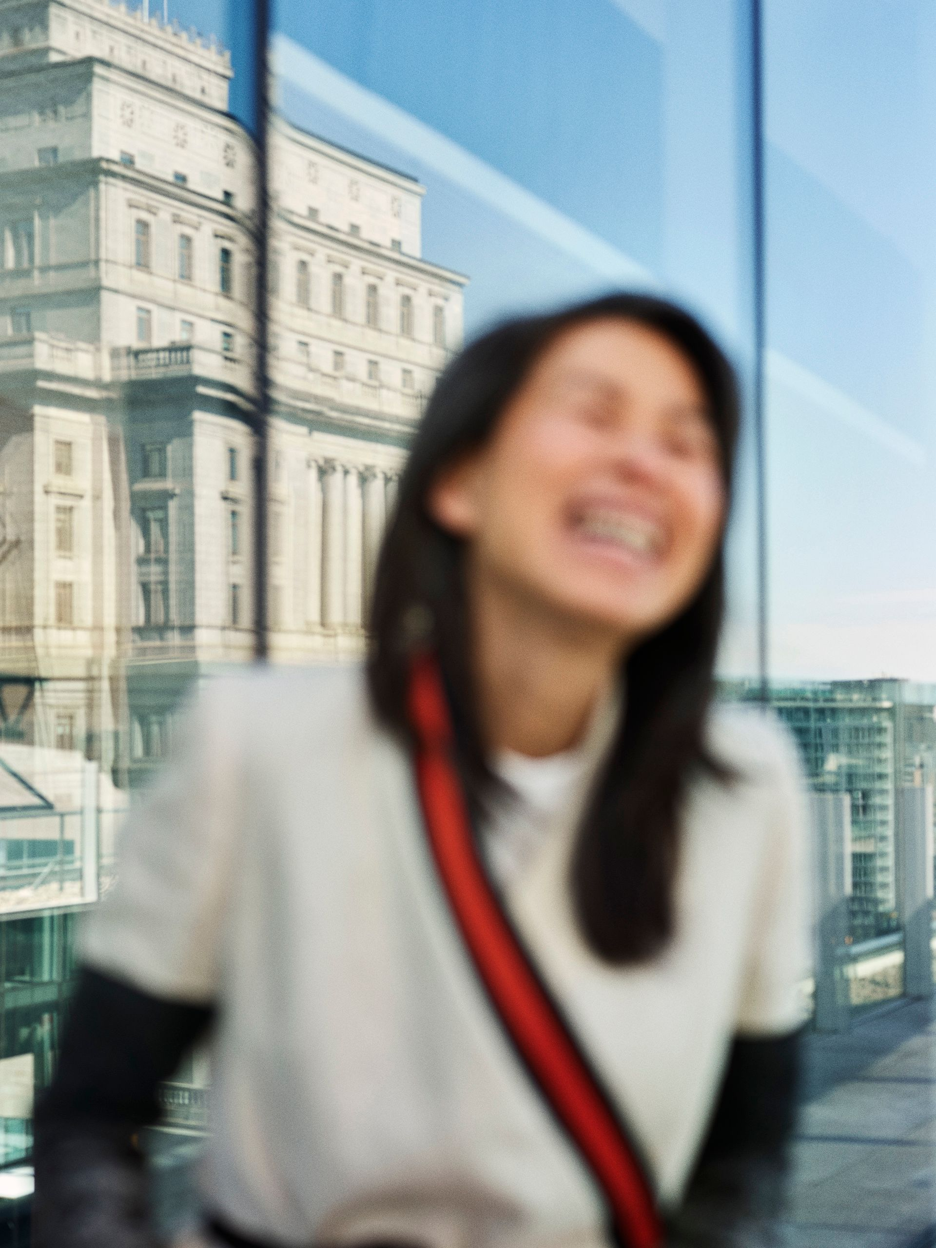 Out of focus portrait of author Kim Thuy laughing in front of glass tower buildings.