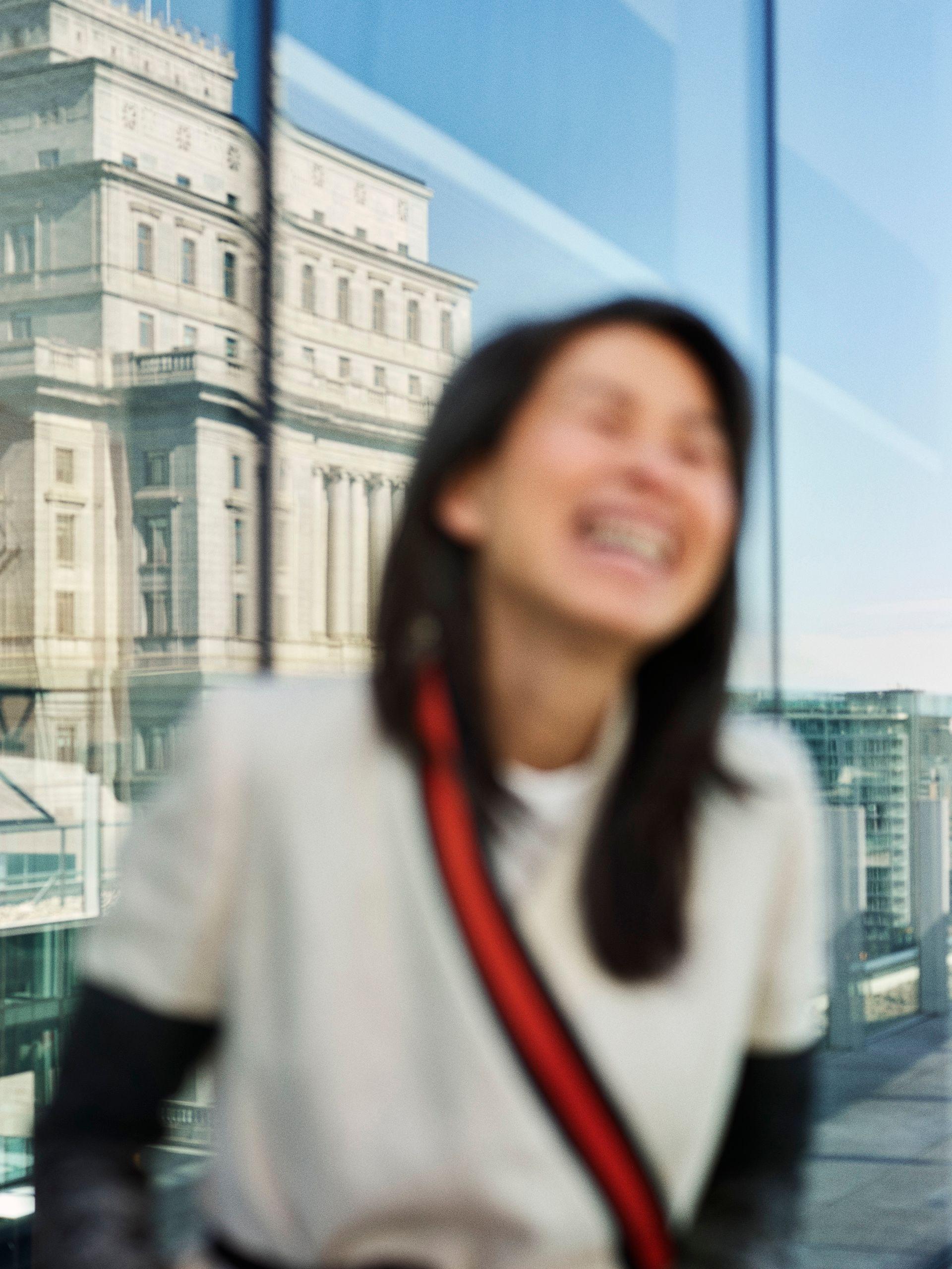 Portrait flou de l'auteur Kim Thuy riant devant des tours de verre.