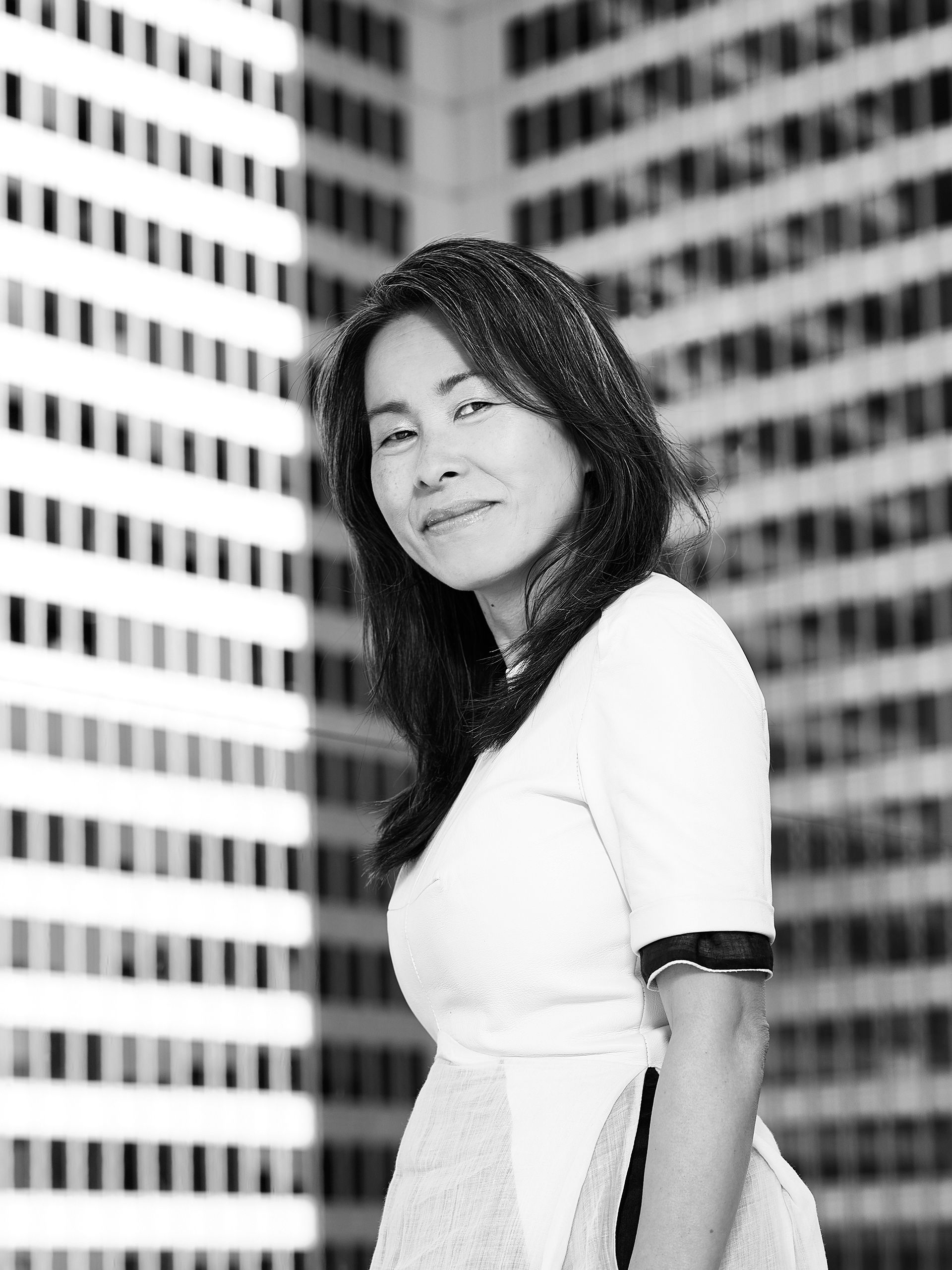 Black and white portrait of author Kim Thuy wearing a white dress in front of downtown buildings.