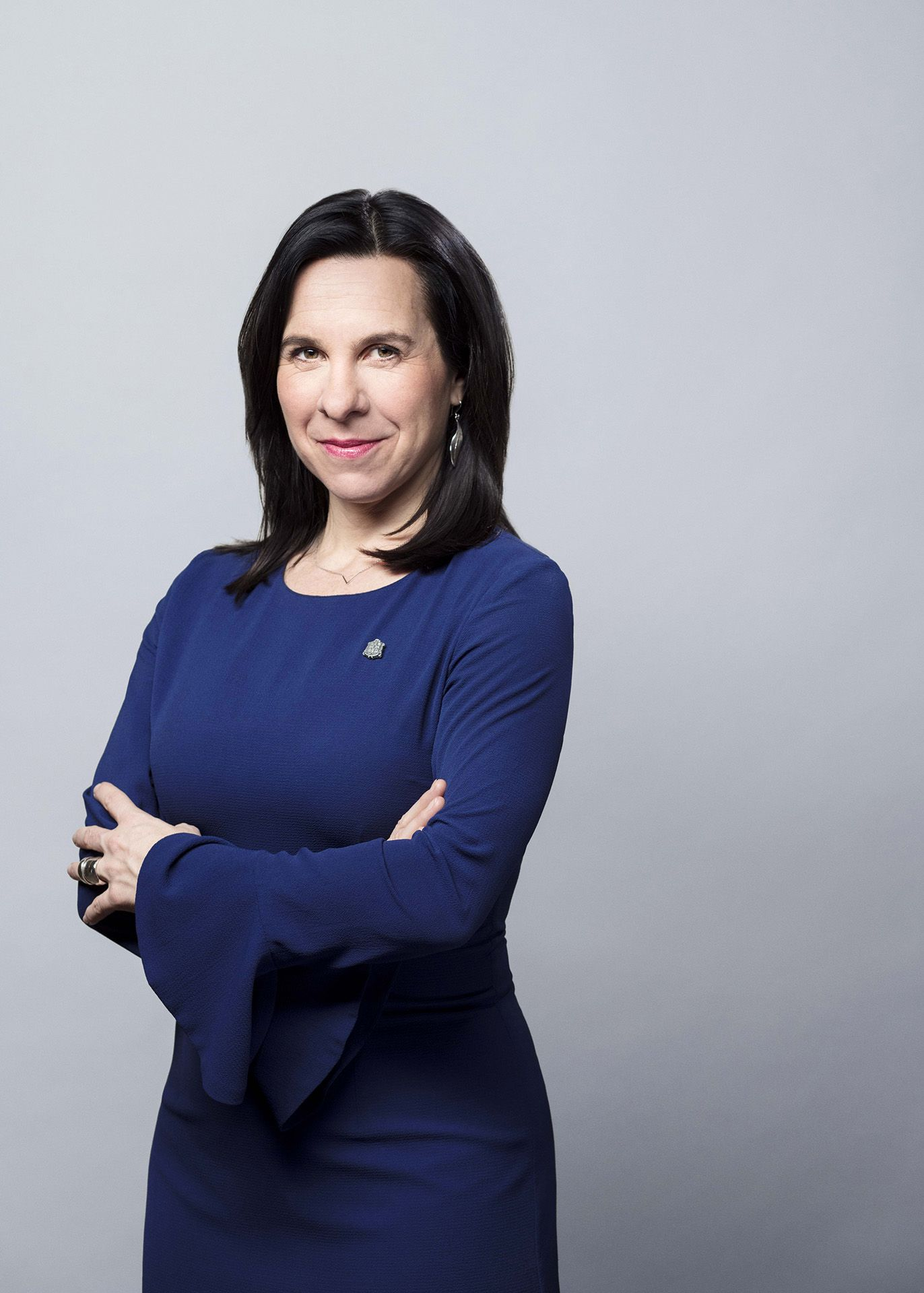 Mid portrait of Montreal mayor Valérie Plante wearing a blue dress and standing with her arms crossed in front of her.