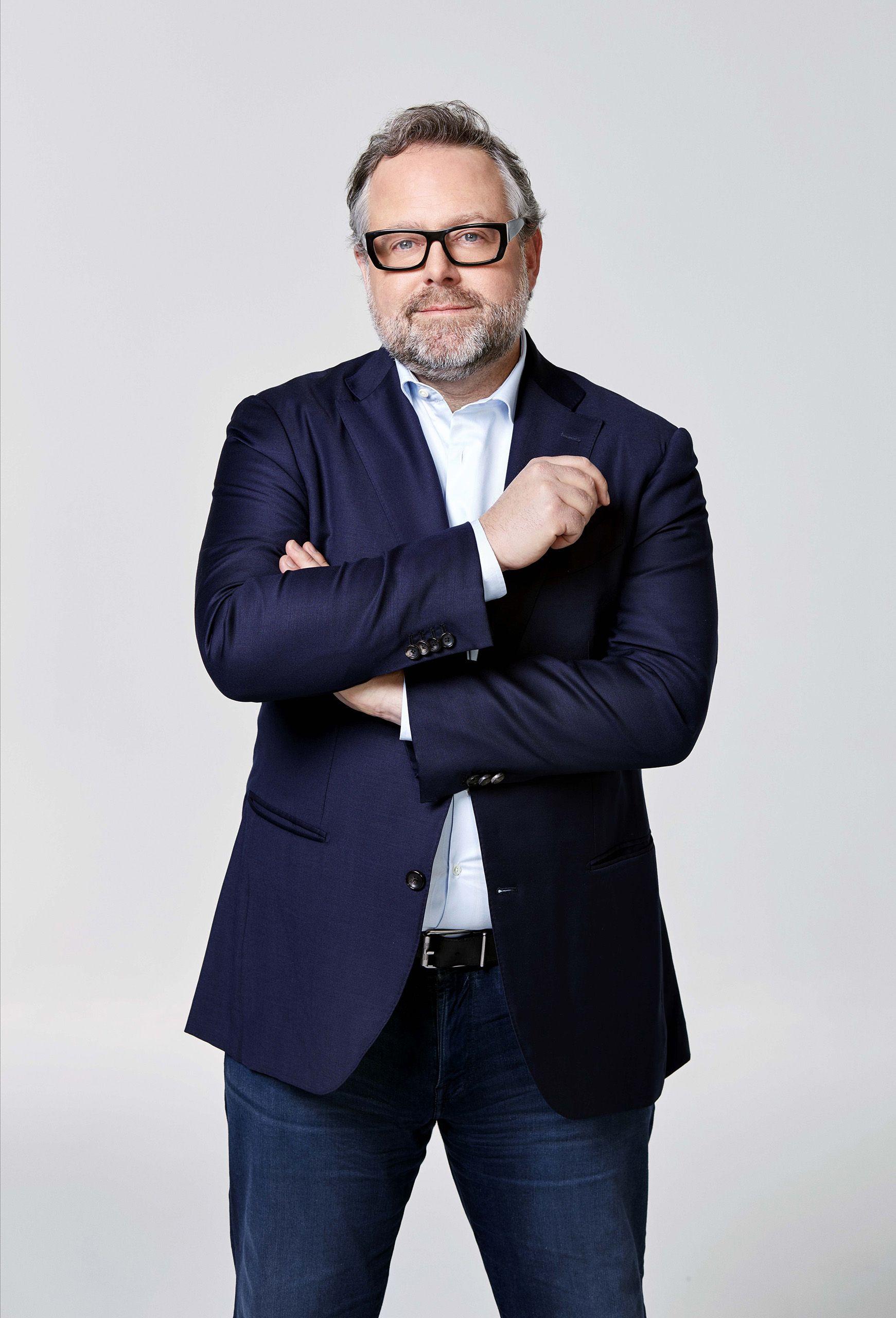 Portrait en mi-longueur d'un homme portant un jean et une chemise, une veste, des lunettes.