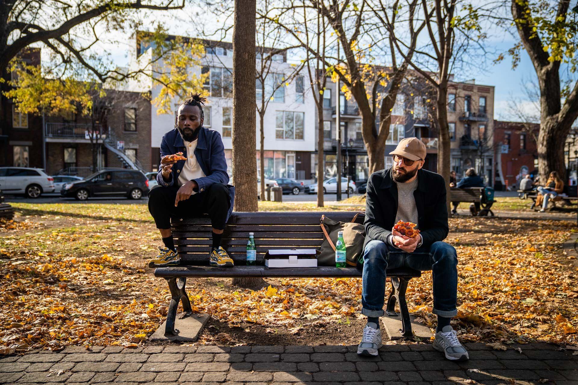 Dahls workwear and aprons photographed by Bruno Florin of man model Julio sitting on bench in park eating pizza wearing dark blue work shirt