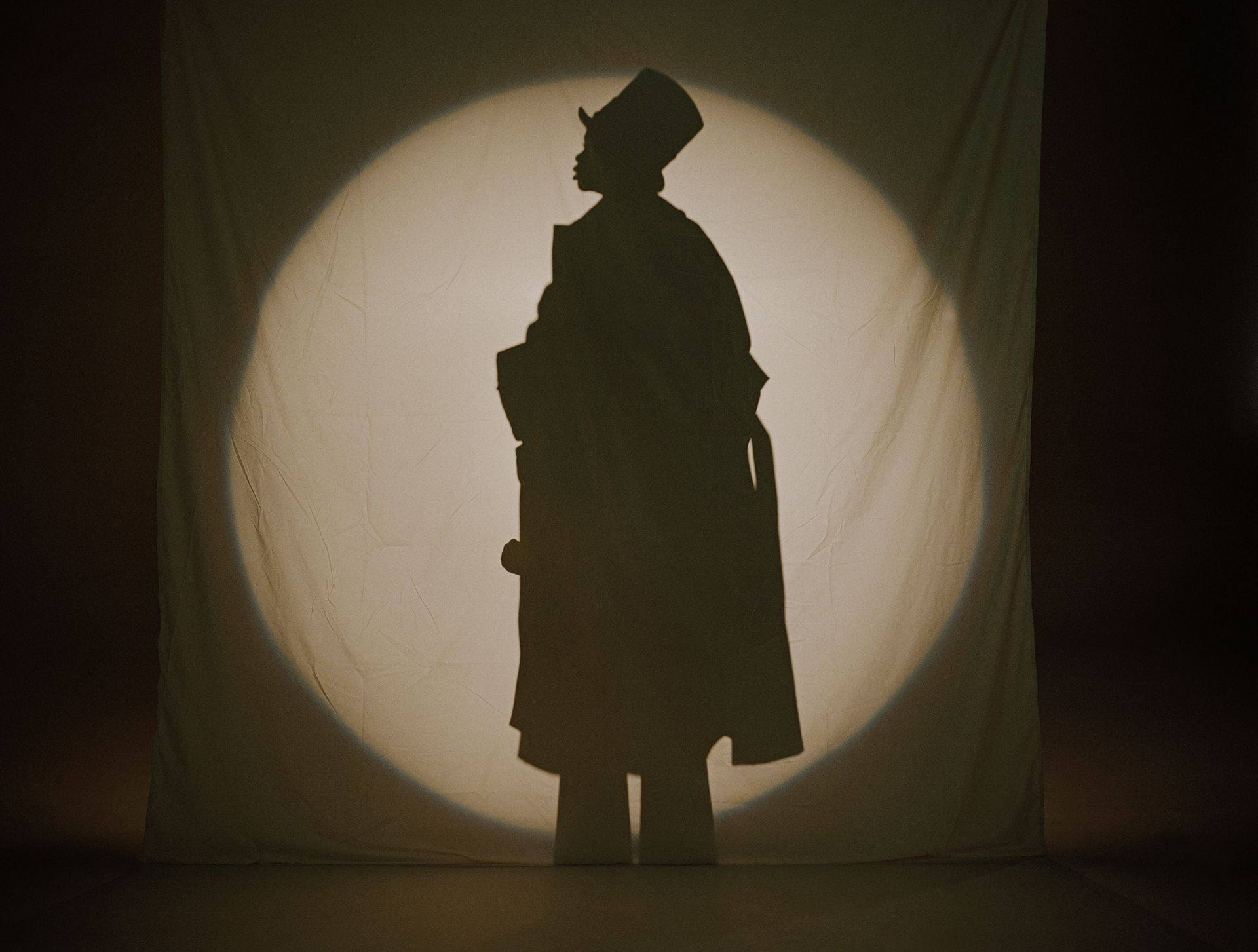 Little boy pretending he is a tall adult in a trench coat in a shadow show. We only see his shadow in a round circle of light.