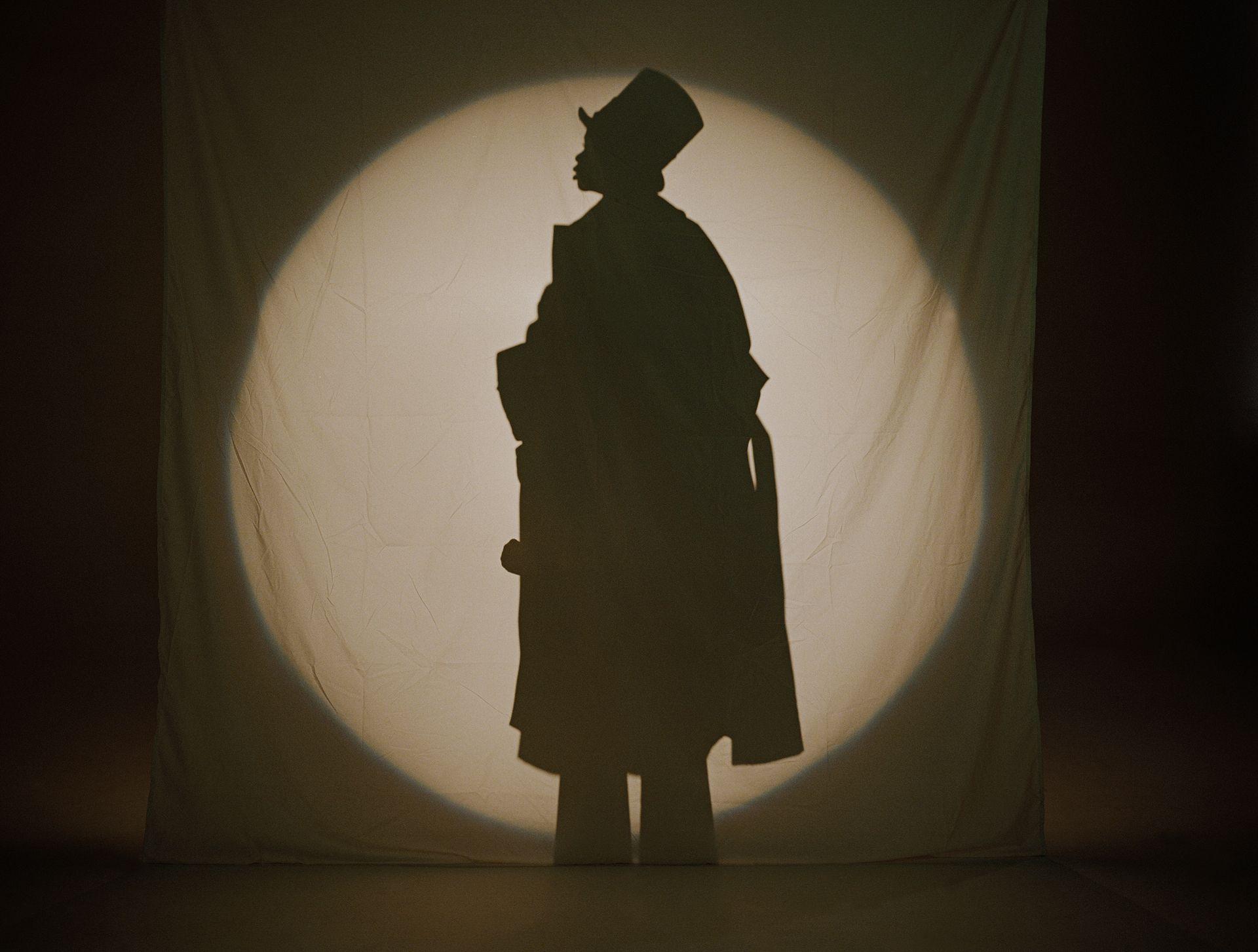 Un petit garçon fait semblant d'être un grand adulte en trench-coat dans un spectacle d'ombres chinoises. Nous ne voyons que son ombre dans un cercle de lumière.