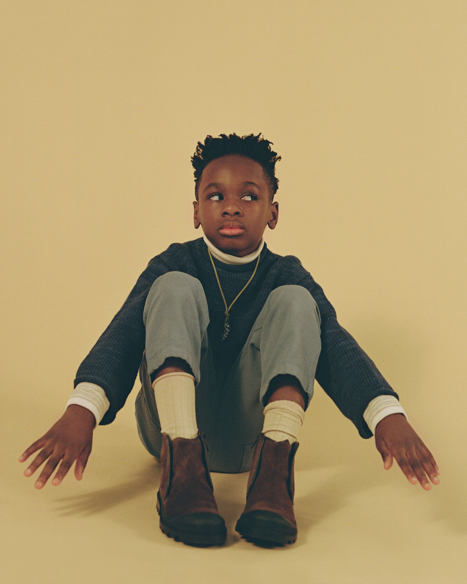 Young black kid looking aside sitting on a beige yellow background with his hands forward in a funny pause.
