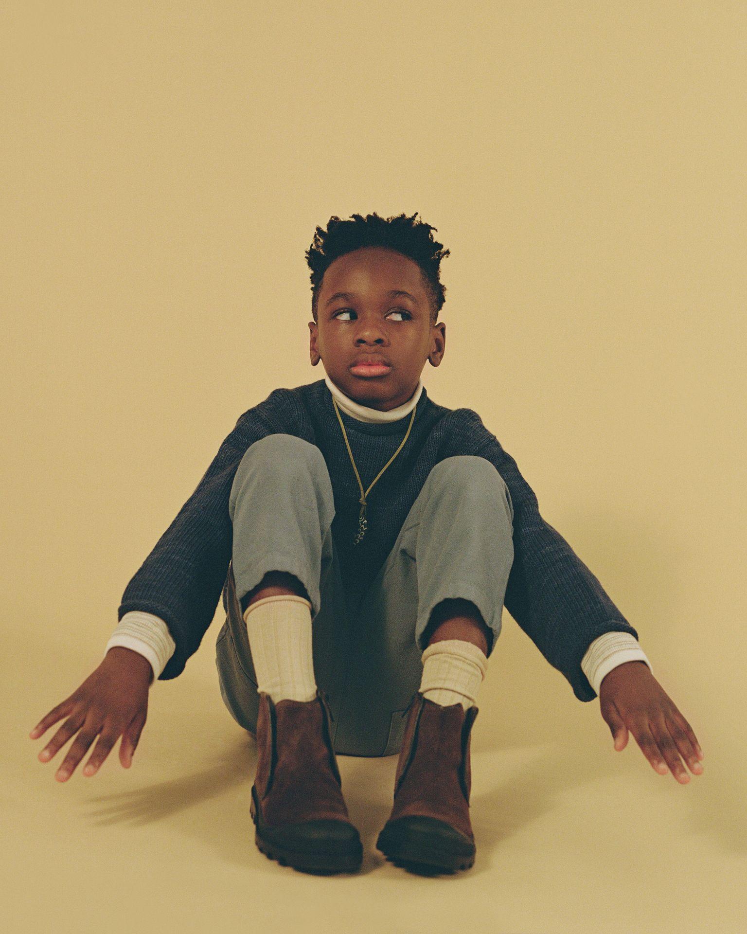 Jeune garçon noir regardant de côté, assis sur un fond jaune beige, les mains en avant dans une pause amusante.
