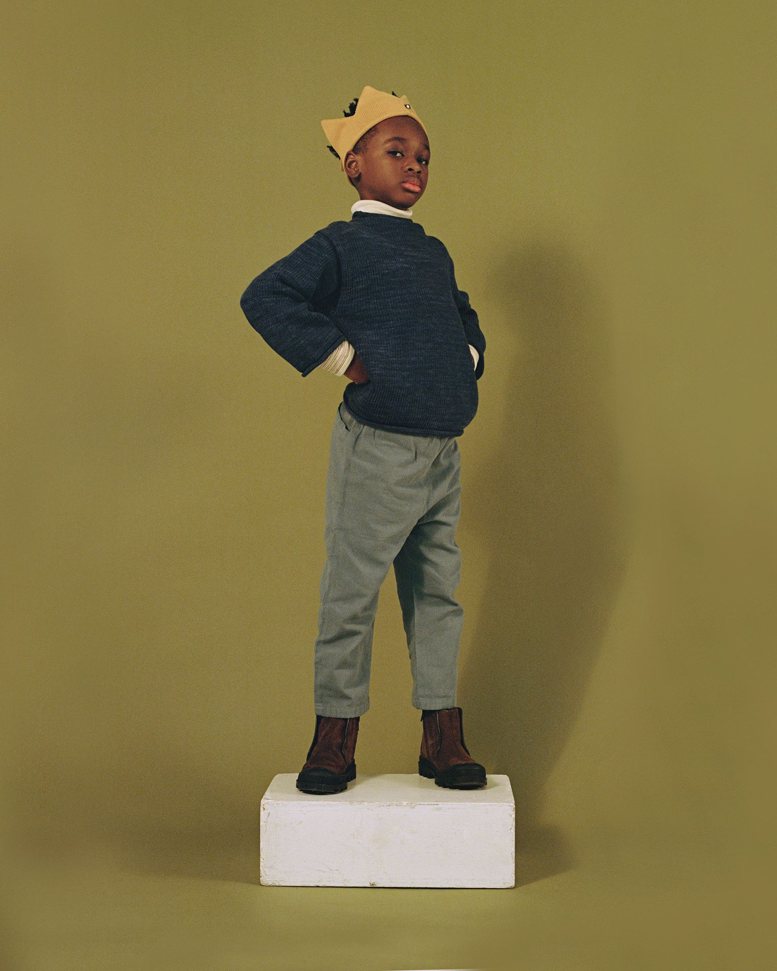 Little bipoc boy proudly standing on white apple boxe. He is wearing a fabric crown.