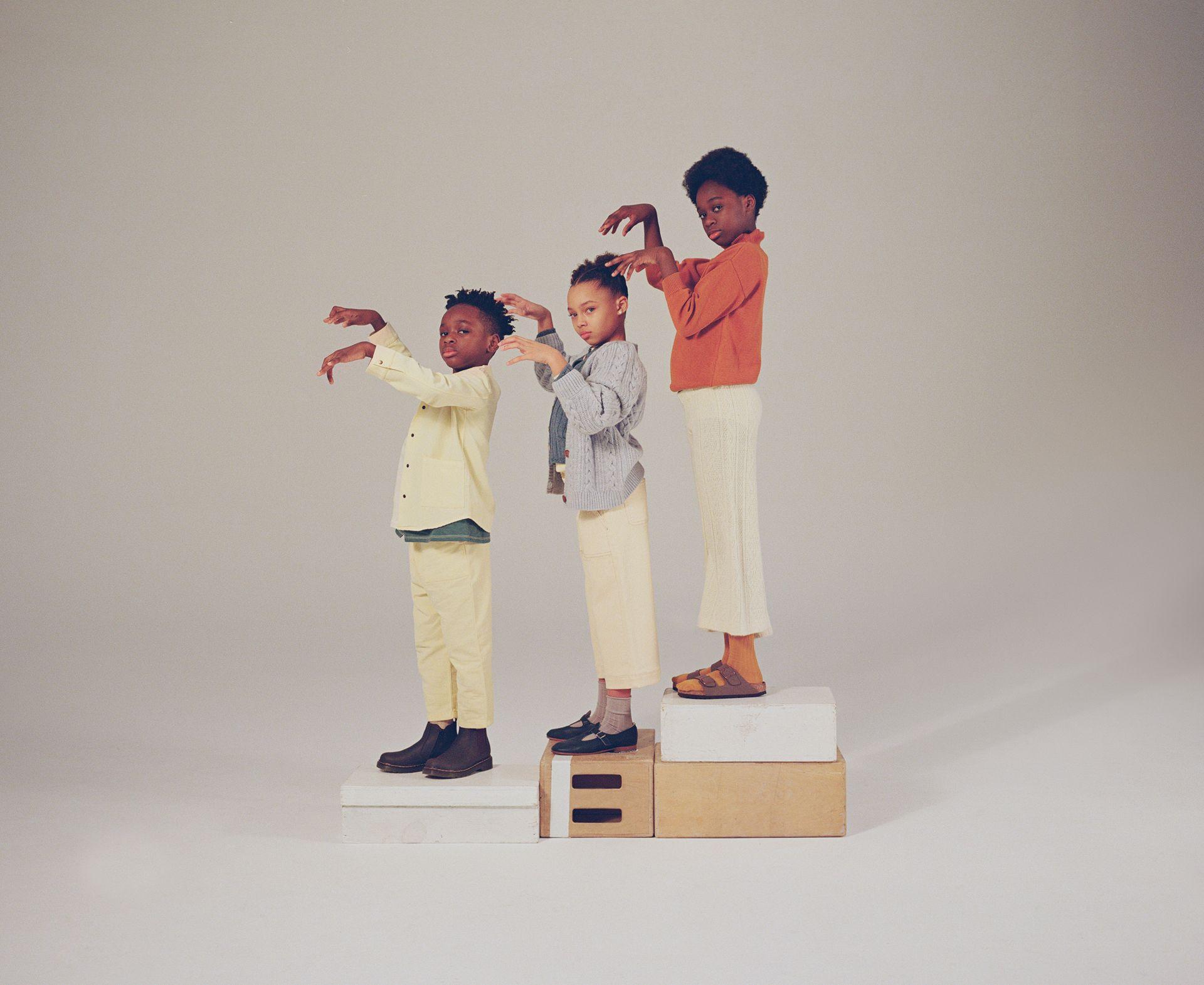 Trois enfants bipèdes qui se tiennent en ligne et de côté sur des boîtes de pommes et qui font des mimiques amusantes avec leurs mains pour un spectacle d'ombres.