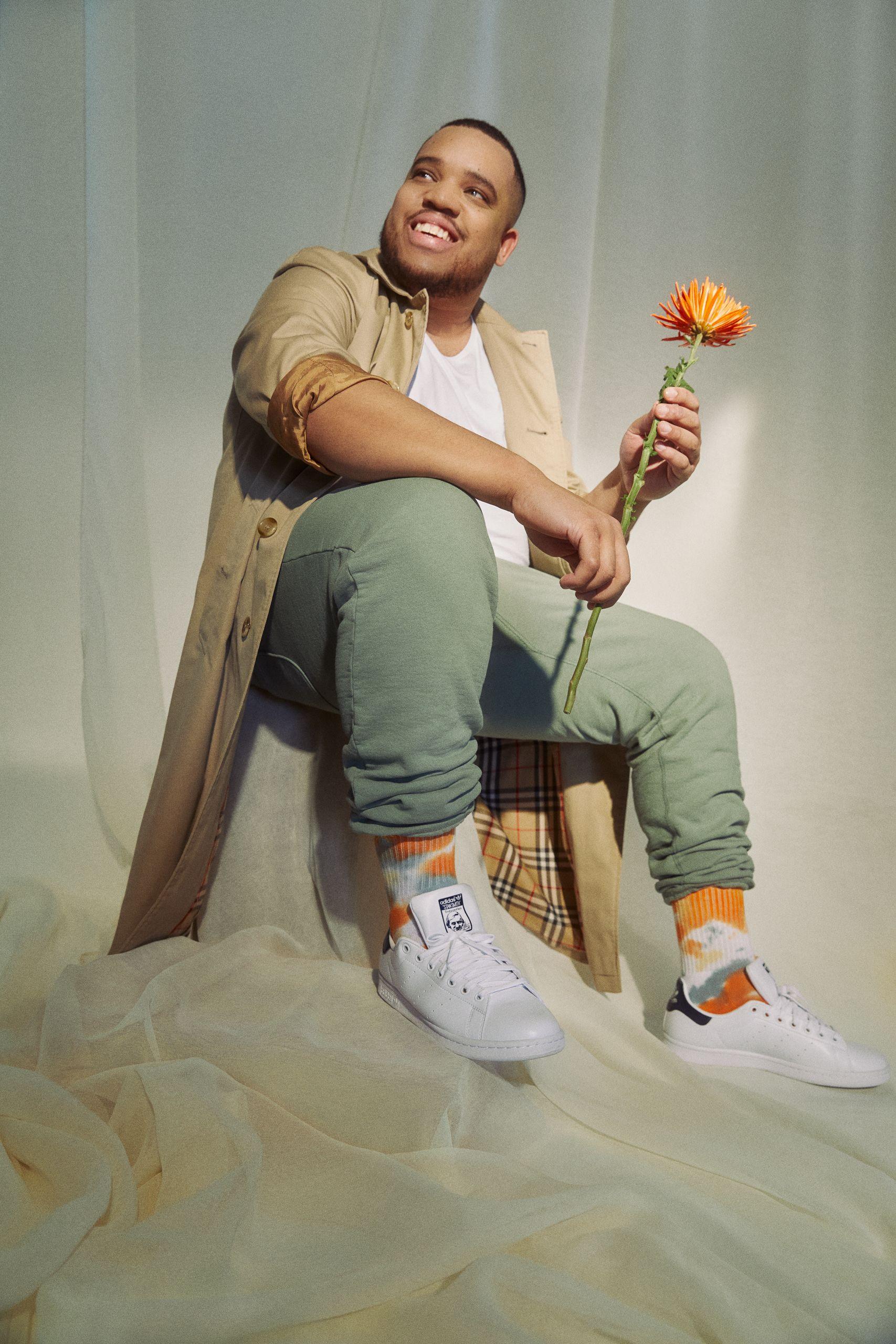 Homme assis sur un fond fait de voiles. Il porte un pantalon de survêtement kaki, un trench-coat beige, des chaussettes orange tie dye dans des baskets blanches. Il sourit et tient une fleur orange.