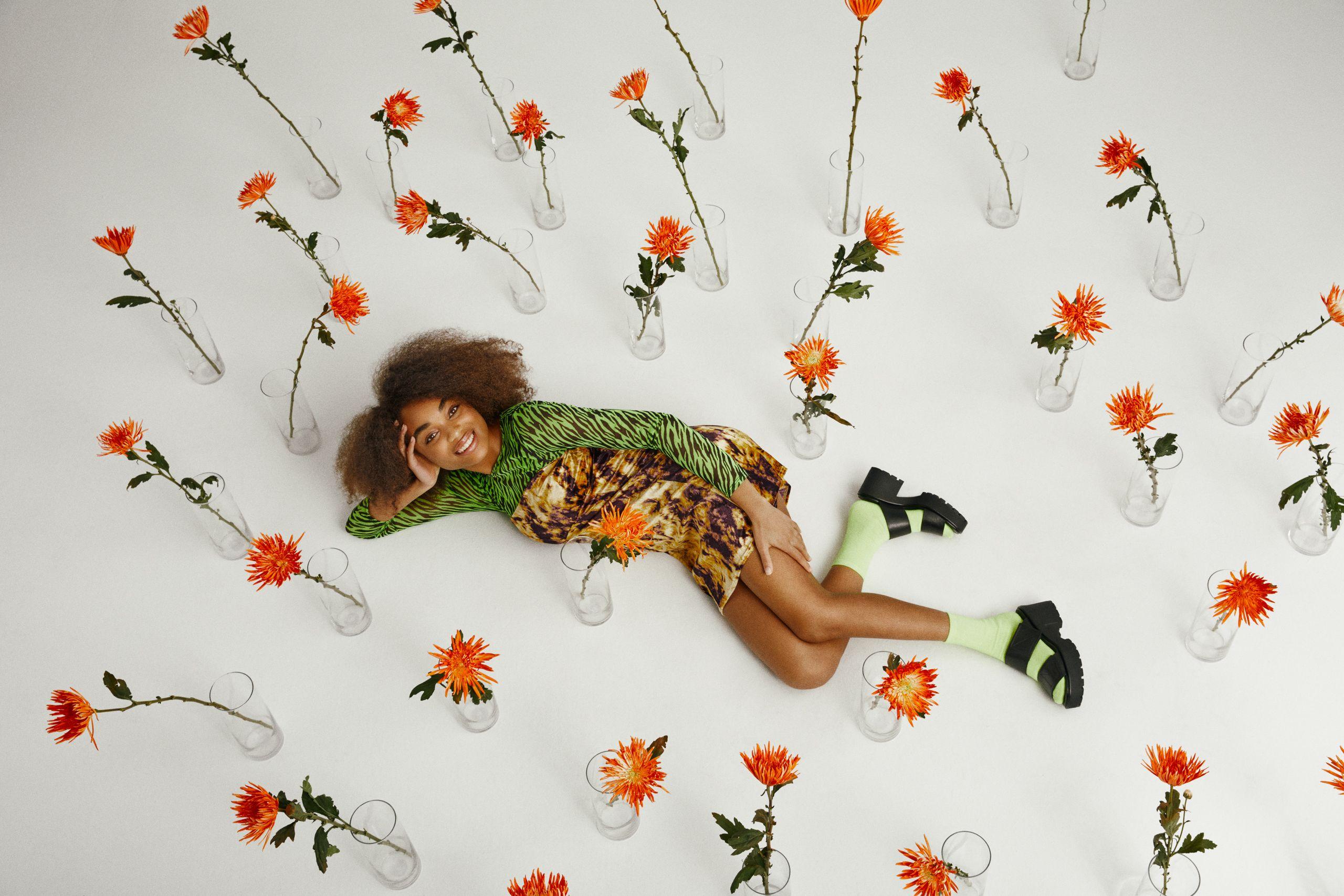Femme allongée sur un sol blanc, portant des sandales à talons noires, des chaussettes vert menthe et une robe à imprimé animal. Des vases contenant chacun une fleur orange sont éparpillés autour d'elle.
