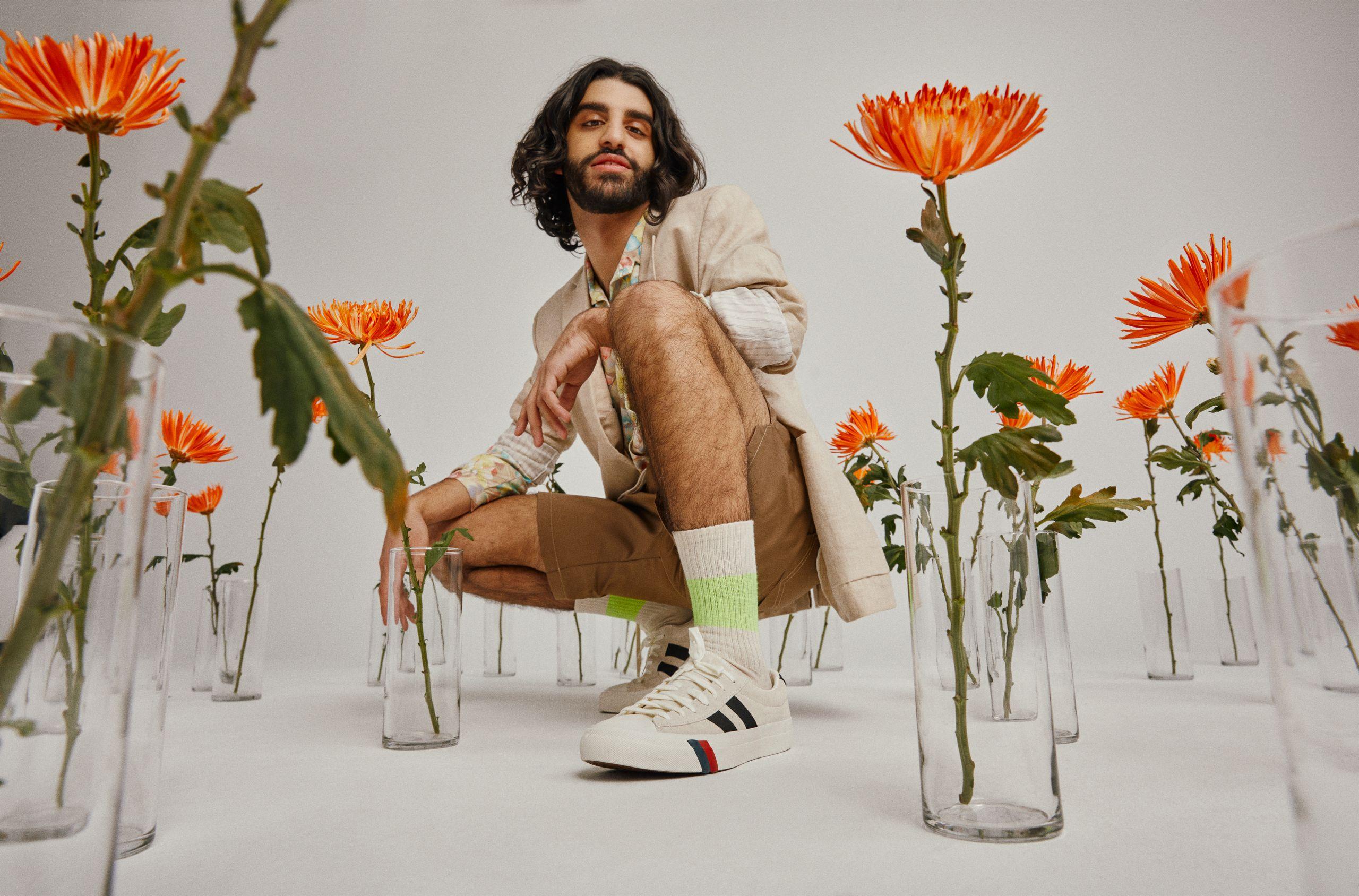 Un homme agenouillé sur un vélo blanc, entouré de vases contenant chacun une fleur orange. Il porte un costume en lin beige avec un short beige foncé et des petites chaussures bordeaux.