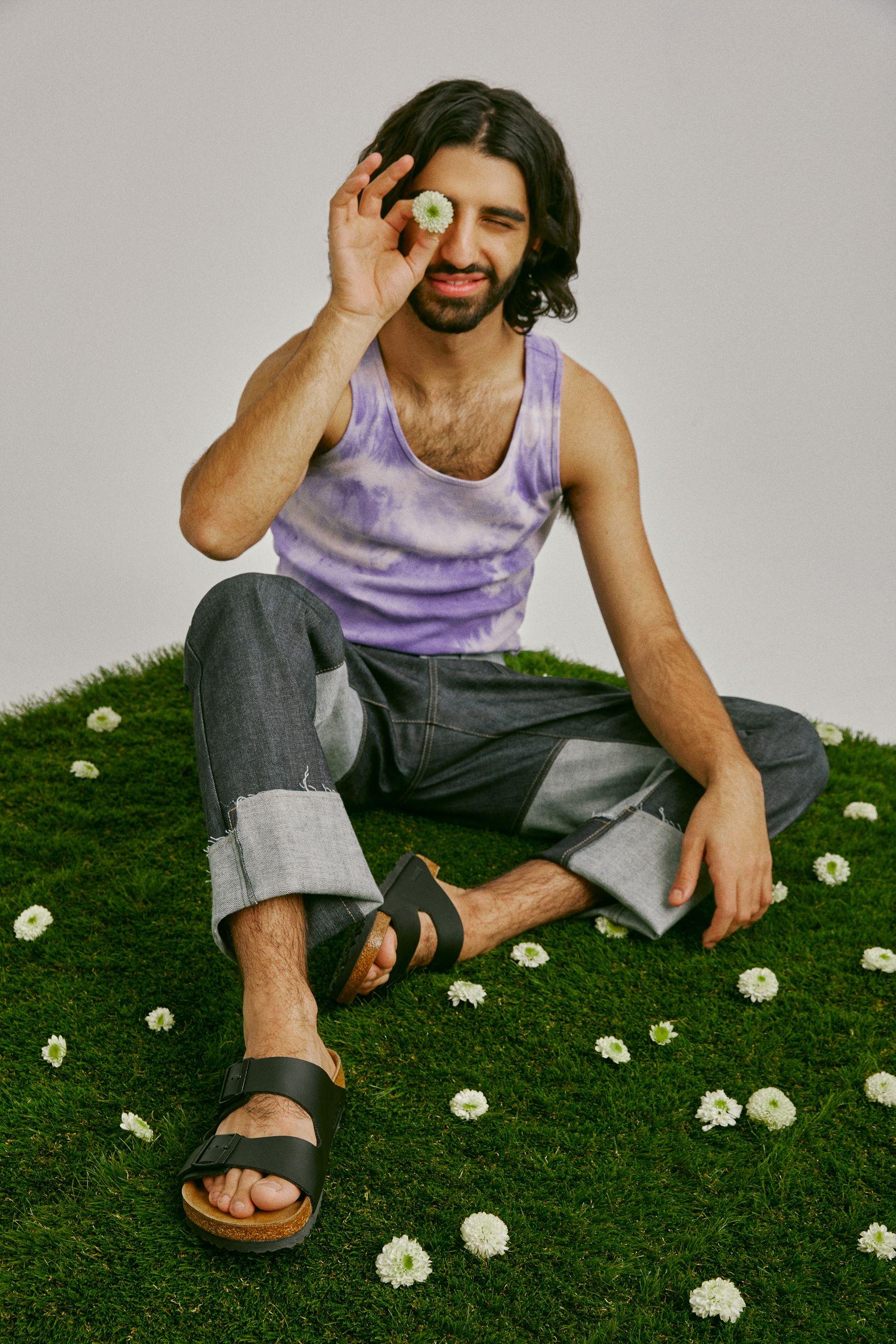 Homme assis sur de la fausse herbe avec des petites fleurs blanches éparpillées autour de lui. Il porte des sandales noires, un jean gris et une camisole lilas. Il tient une fleur devant un œil.