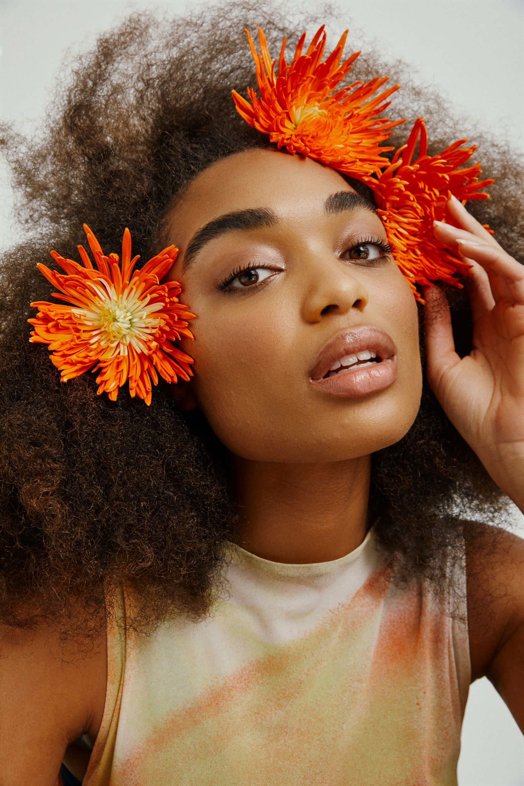 Plan de beauté d'une femme avec des fleurs orange dans ses cheveux bouclés.