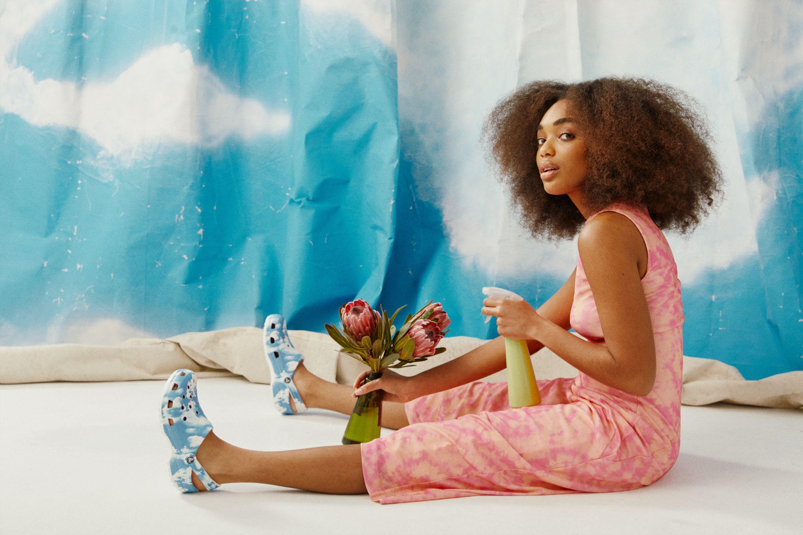 Femme assise sur un vélo blanc avec la toile peinte d'un ciel bleu et de nuages blancs derrière elle. Elle porte des crocs de ciel bleu et de nuages blancs avec une robe rose, elle est sur le point de pulvériser les fleurs qu'elle tient.
