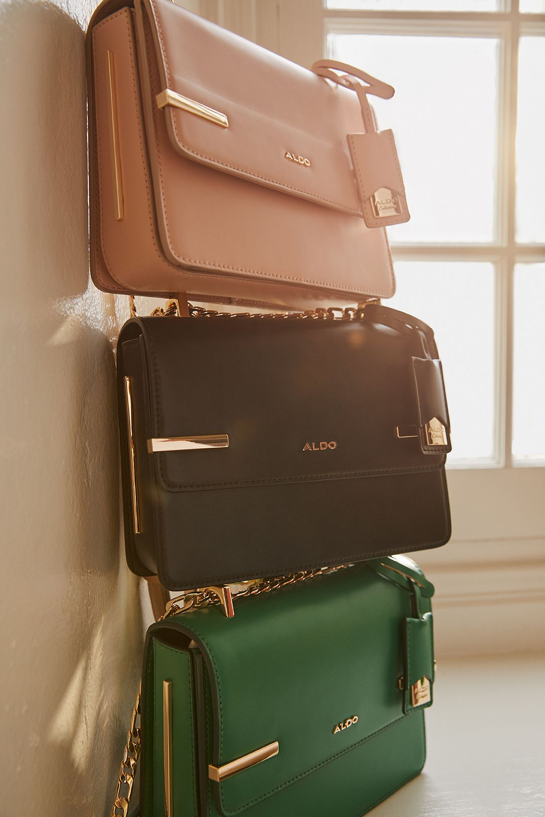 Three of the same smooth leatherette aldo purse. Metal gold accessories, in green, black and coral colours. Piled up in a white room.