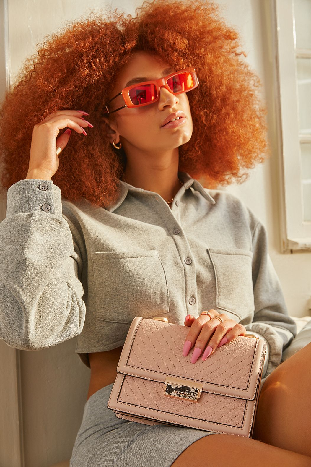 Copper red afro with red sunglasses, Aldo purse, pink fake nails.The woman is posing with attitude.