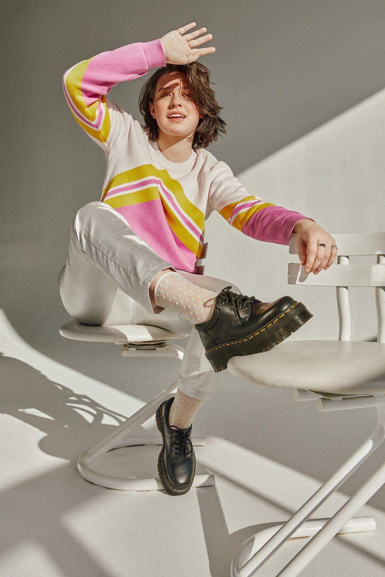 Femme souriante avec du soleil dans les yeux, portant une chemise rayée rose, beige et jaune, un pantalon argenté, des chaussettes transparentes à pois et des dock martens. Elle est assise sur une chaise blanche sur un fond blanc, agitant sa main, un pied sur une autre chaise.