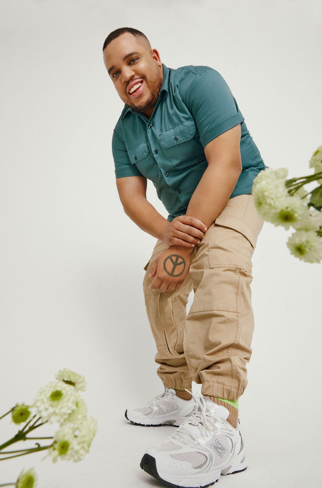 Homme souriant, incliné vers le bas et regardant l'appareil photo. Il est debout sur un fond blanc et porte une chemise bleue à manches courtes, un pantalon beige et des baskets blanches New Balance.