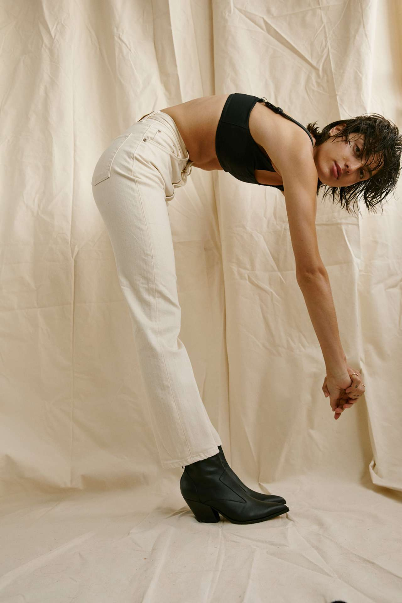 Premiere Adresse high fashion shop photographs by Kelly Jacob of man model crouching on the ground wearing cream button-up shirt and cream pants