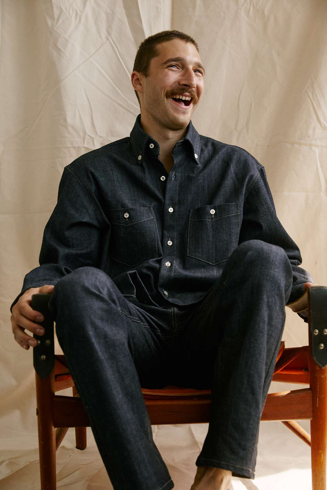 Premiere Adresse high fashion shop photographs by Kelly Jacob of man model sitting in chair wearing black denim button-up shirt and black denim pants