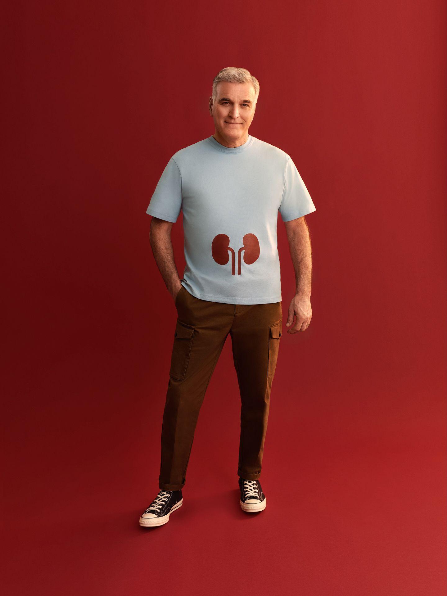 Homme aux cheveux gris portant un t-shirt bleu pâle sur lequel sont imprimés des reins. Il est debout sur un fond rouge sang.