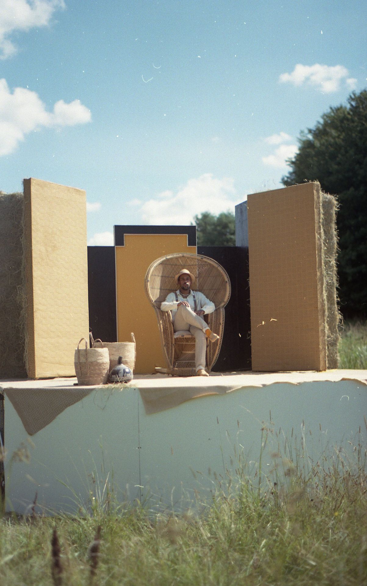 decor and set design in field by Studio TB with singer KNLO sitting on moving rattan throne in his music video Plafond