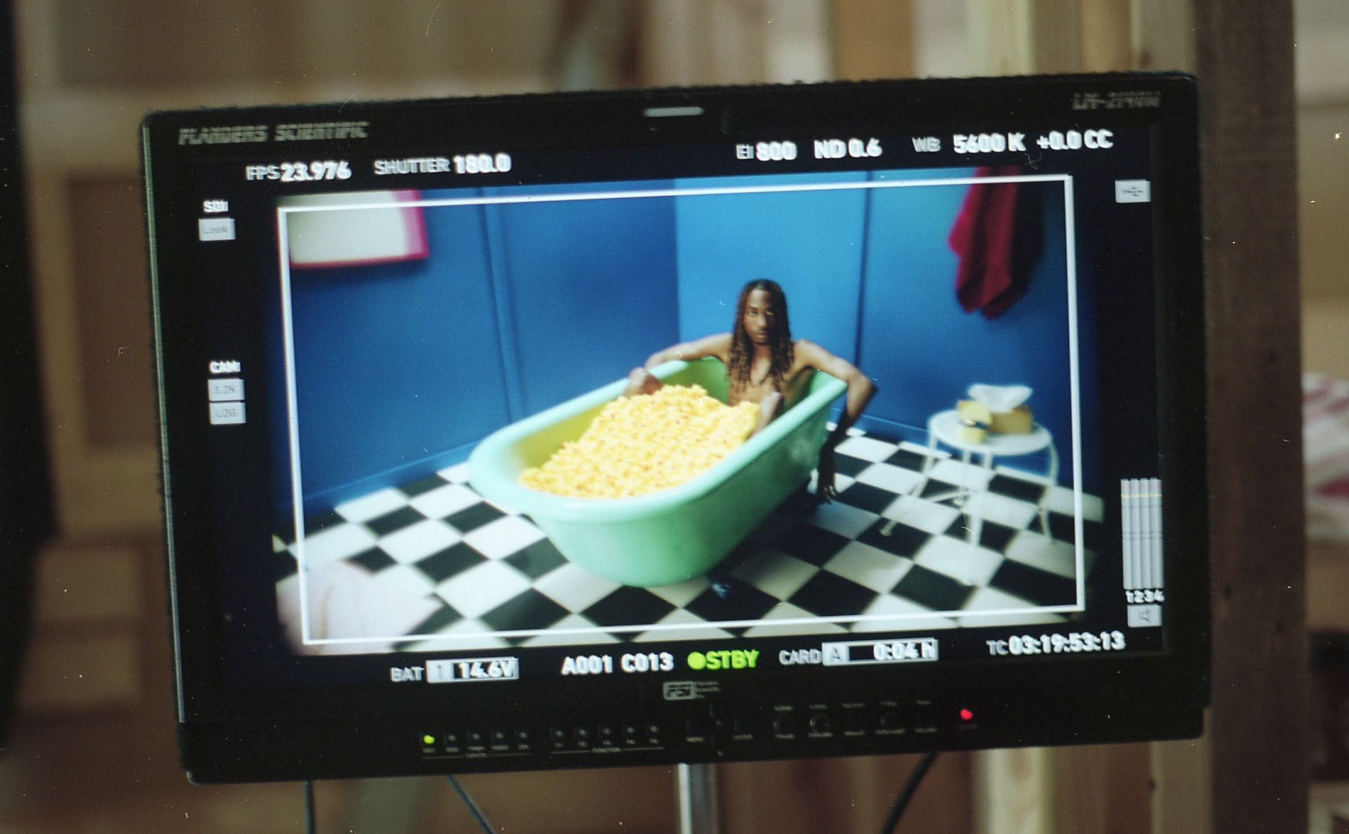 singer TIZZO in a blue bathtub full of plastic ducks for video clip of Uber by Laurence Nerbonne in a set designed by Studio TB