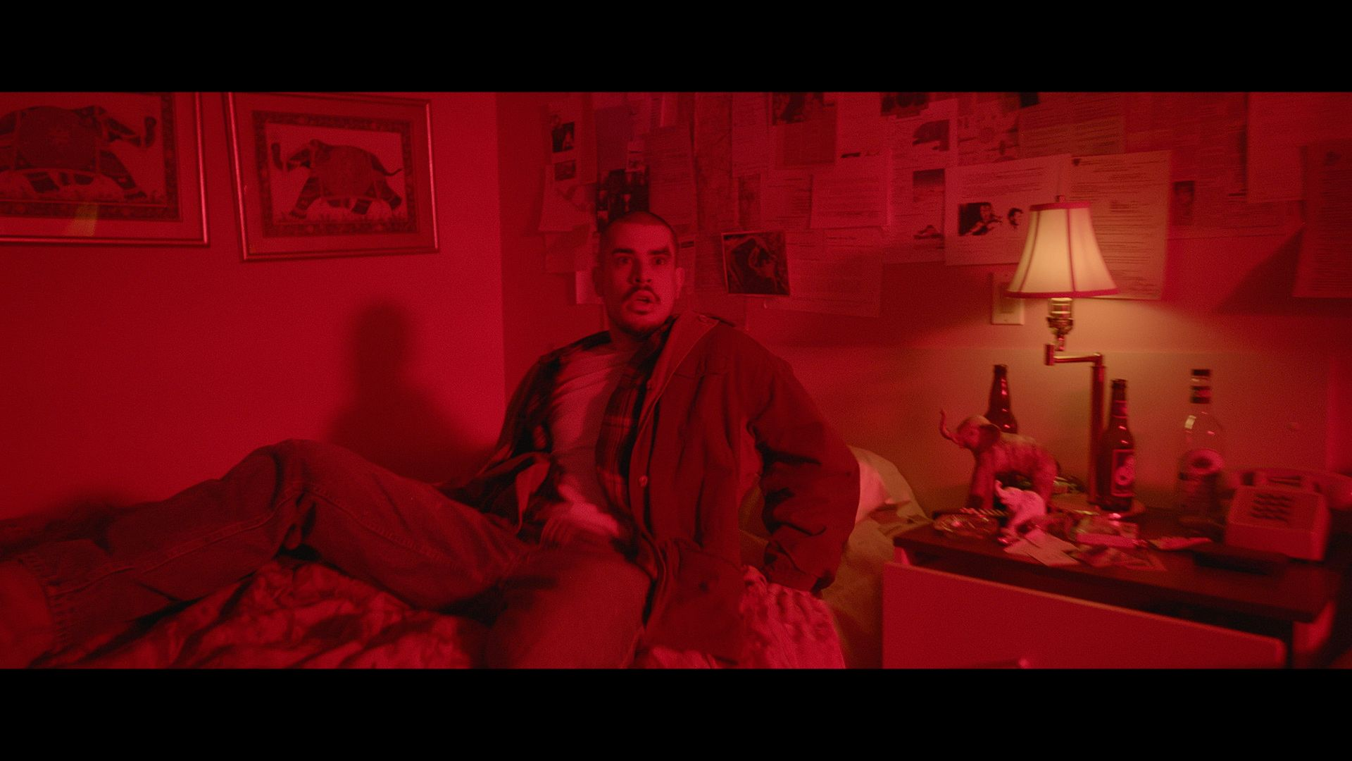 rapper Koriass with wound on his head waking in bed in room basket in red lighting for music video of Elephant filmed by Les Gamins