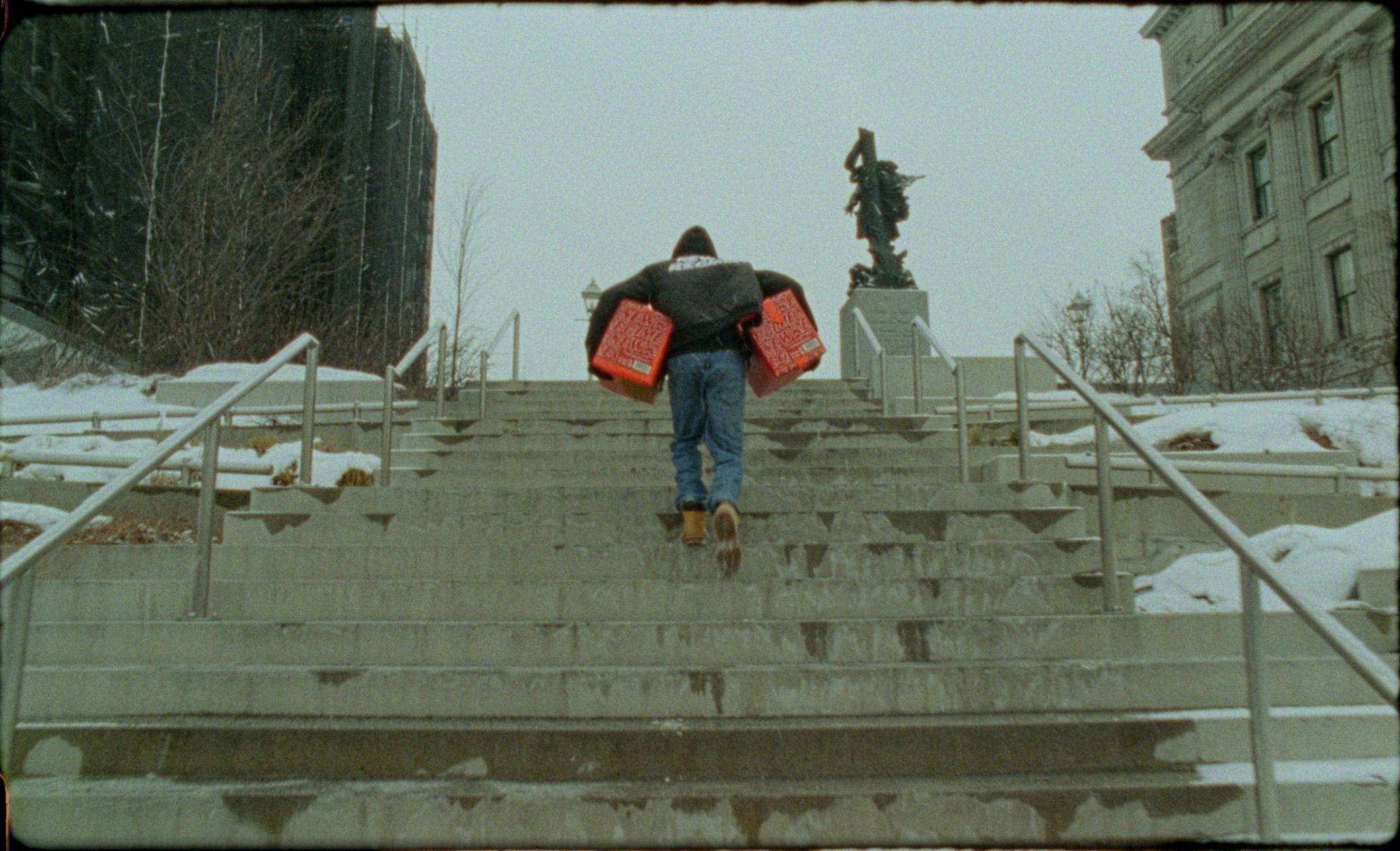 Homme montant un escalier extérieur en hiver à Montréal avec un peu de neige et deux caisses de Havana Club édition limitée sous chaque bras.