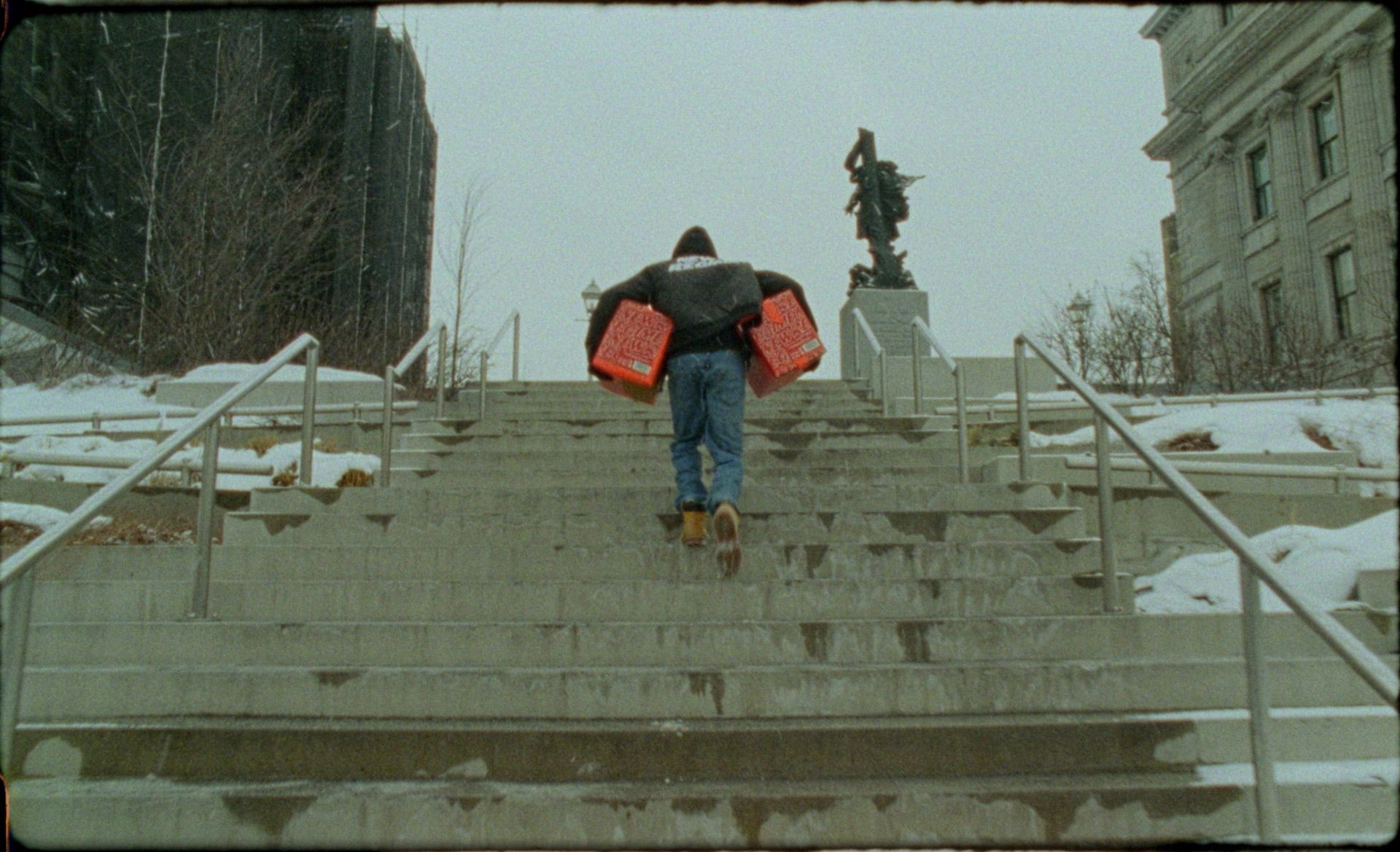 Man climbing up an outdoor staircase in Montreal's winter with a little bit of snow and two cases of Havana Club limited edition under each arm.