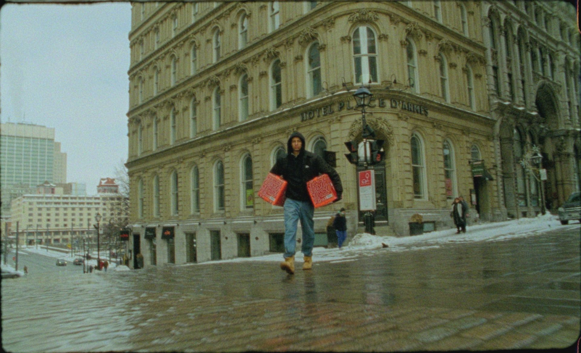 Man walking with a case of Havana Club special edition under each arm and walking in Montreal's winter.