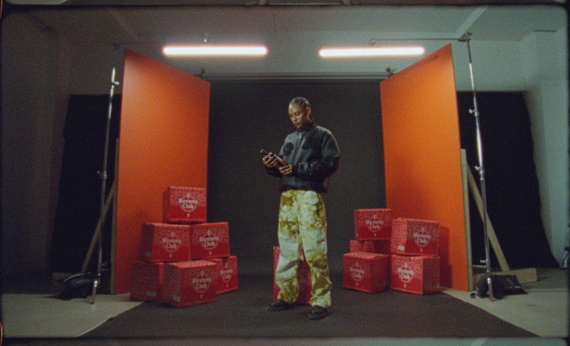 Modèle en studio portant une veste noire et un pantalon baggy regardant une bouteille de Havana Club avec des caisses du produit sur les côtés.