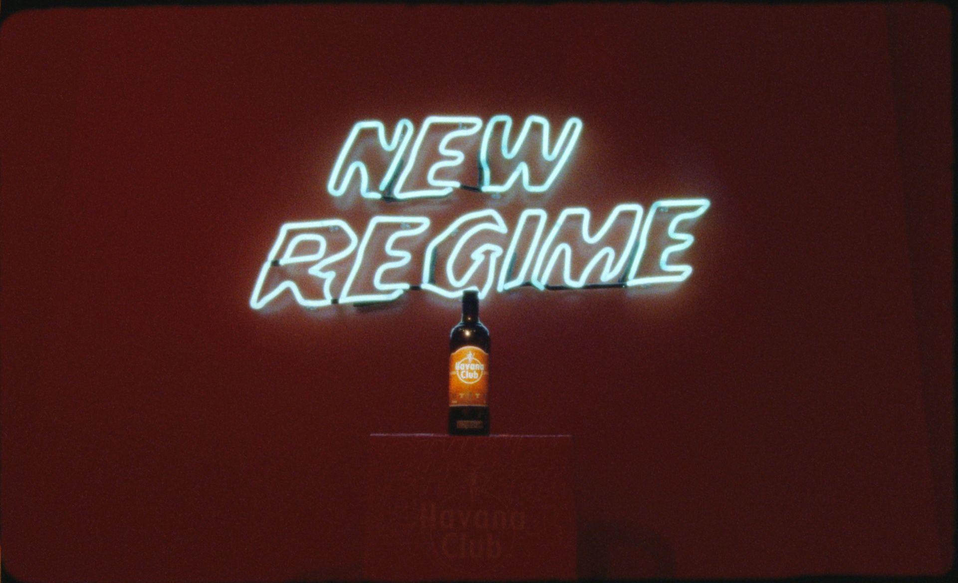 Bouteille d'édition spéciale Havana Club sur un piédestal avec le logo de l'Atelier New Regime en arrière-plan sur un mur rouge foncé.