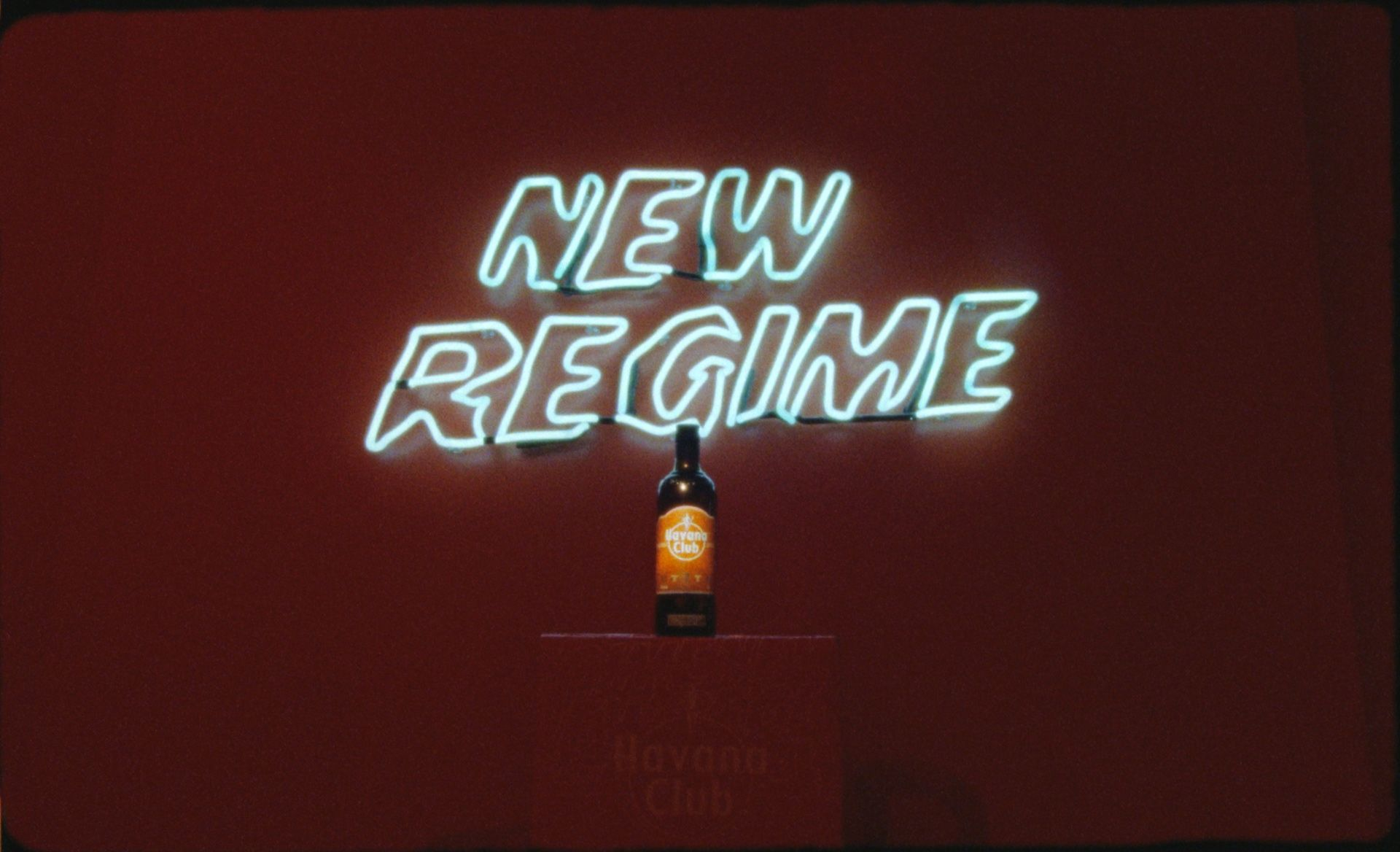 Bottle of Havana Club special edition on a pedestal with the Atelier New Regime logo in the back ground on a dark red wall.