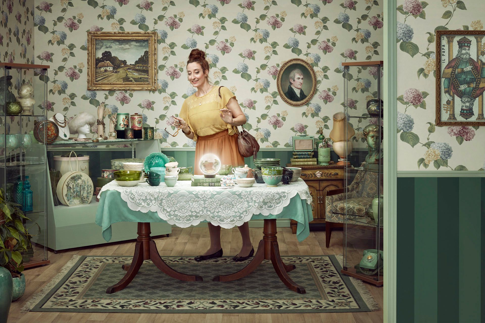 female model standing behind table looking at crystal ball surrounded by old stuff in antique shop for Loto Quebec campaign photographed by Simon Duhamel