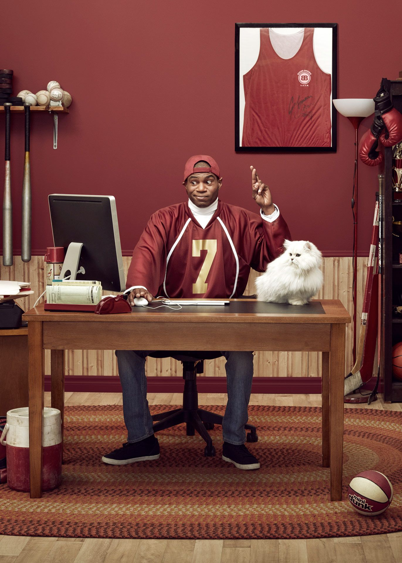 black man sitting at desk with white cat crossing his fingers while looking at computer surrounded by sport's paraphernalia for Loto Quebec campaign photographed by Simon Duhamel