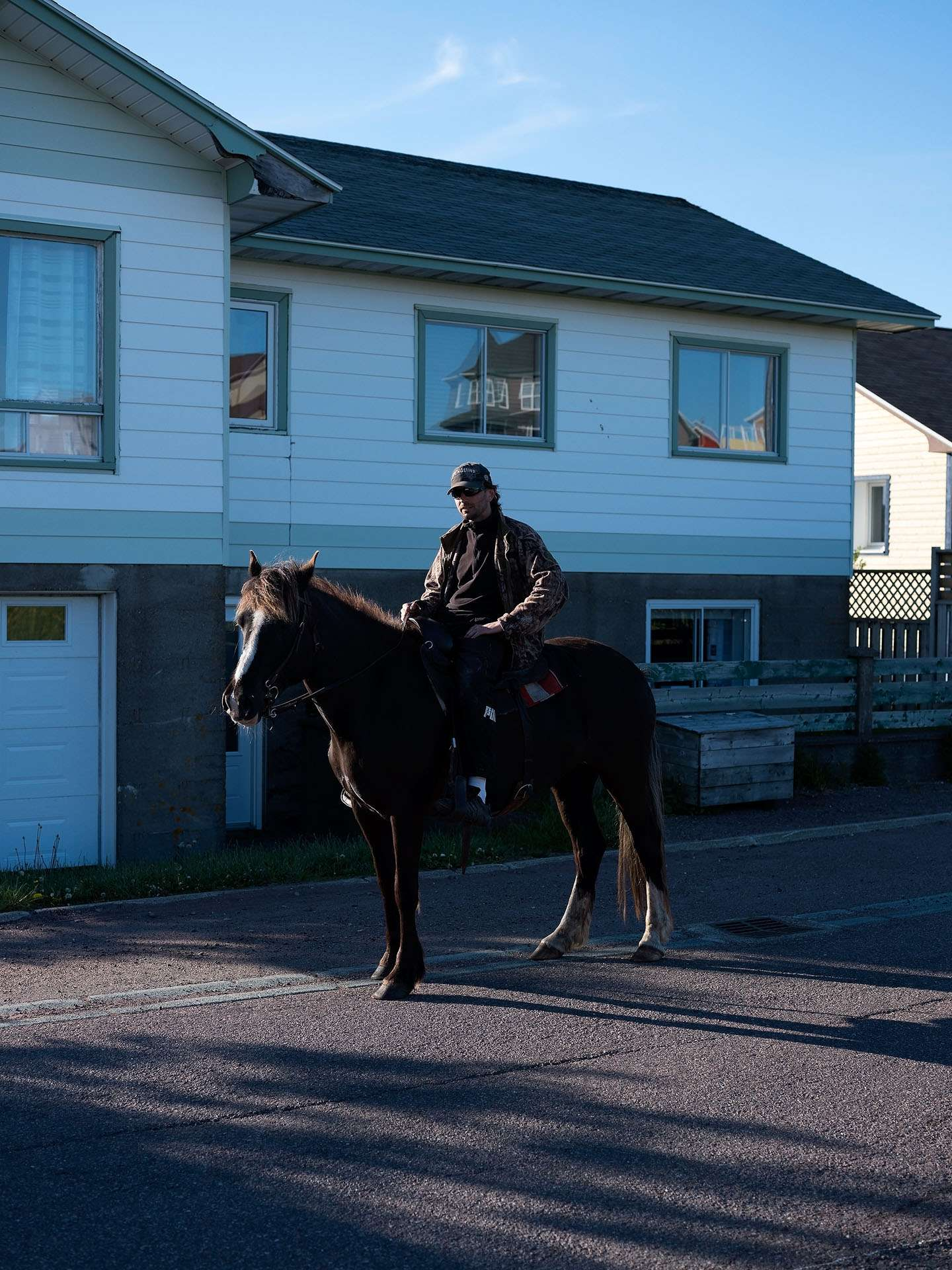 man horseback riding in the street wearing sunglasses by Guillaume Simoneau in Saint-Pierre-et-Miquelon for M le mag Le Monde