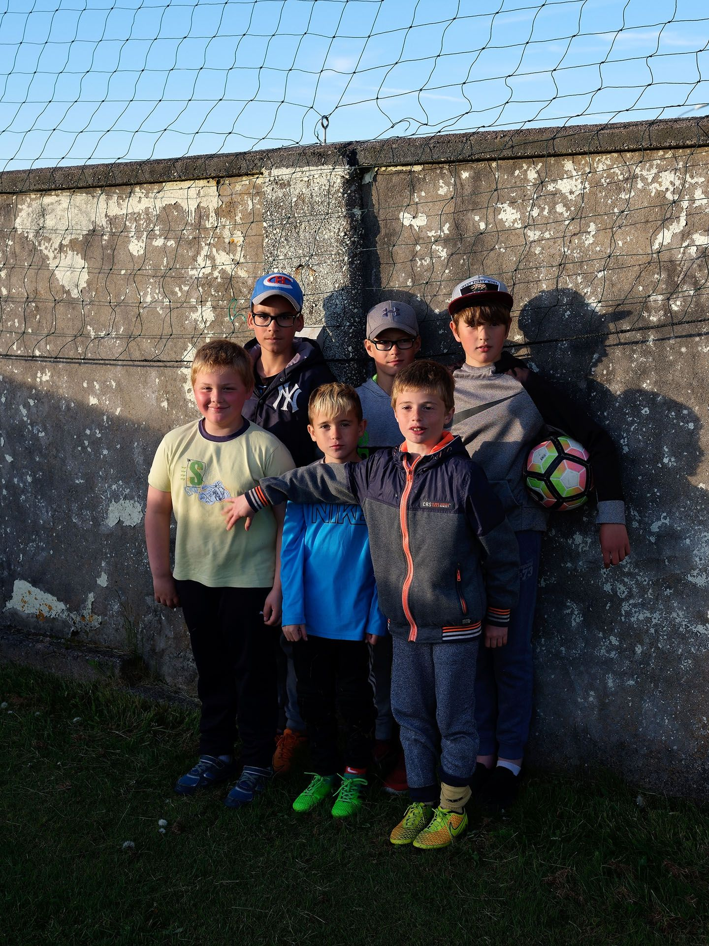 group of young kids posing against a wall with soccer ball by Guillaume Simoneau in Saint-Pierre-et-Miquelon for M le mag Le Monde