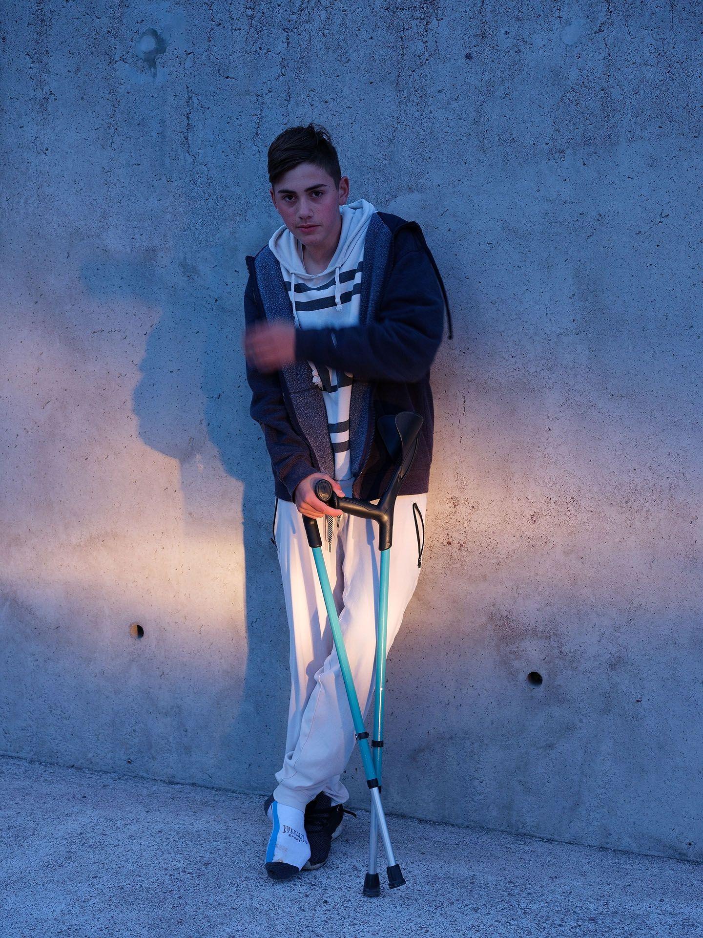 young boy posing against wall using blue crutches by Guillaume Simoneau in Saint-Pierre-et-Miquelon for M le mag Le Monde