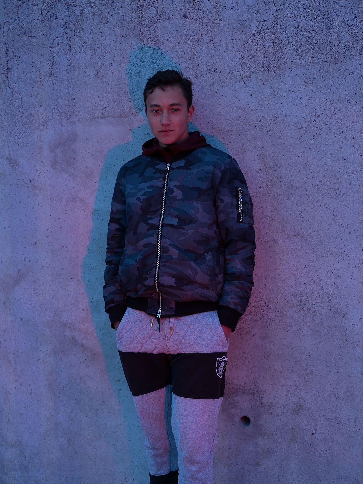young teenage boy posing against wall in lightly red light by Guillaume Simoneau in Saint-Pierre-et-Miquelon for M le mag Le Monde