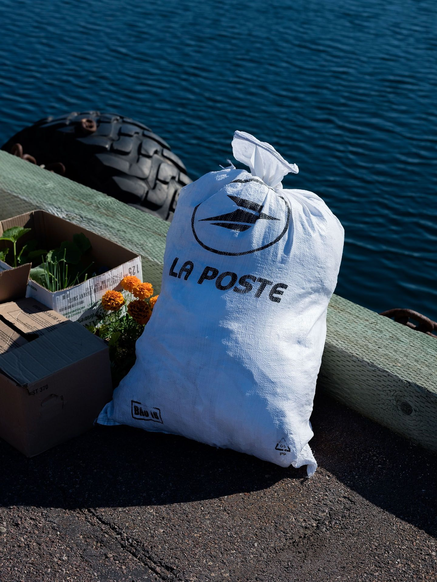 postal office bag full of letters on the dock next to water by Guillaume Simoneau in Saint-Pierre-et-Miquelon for M le mag Le Monde