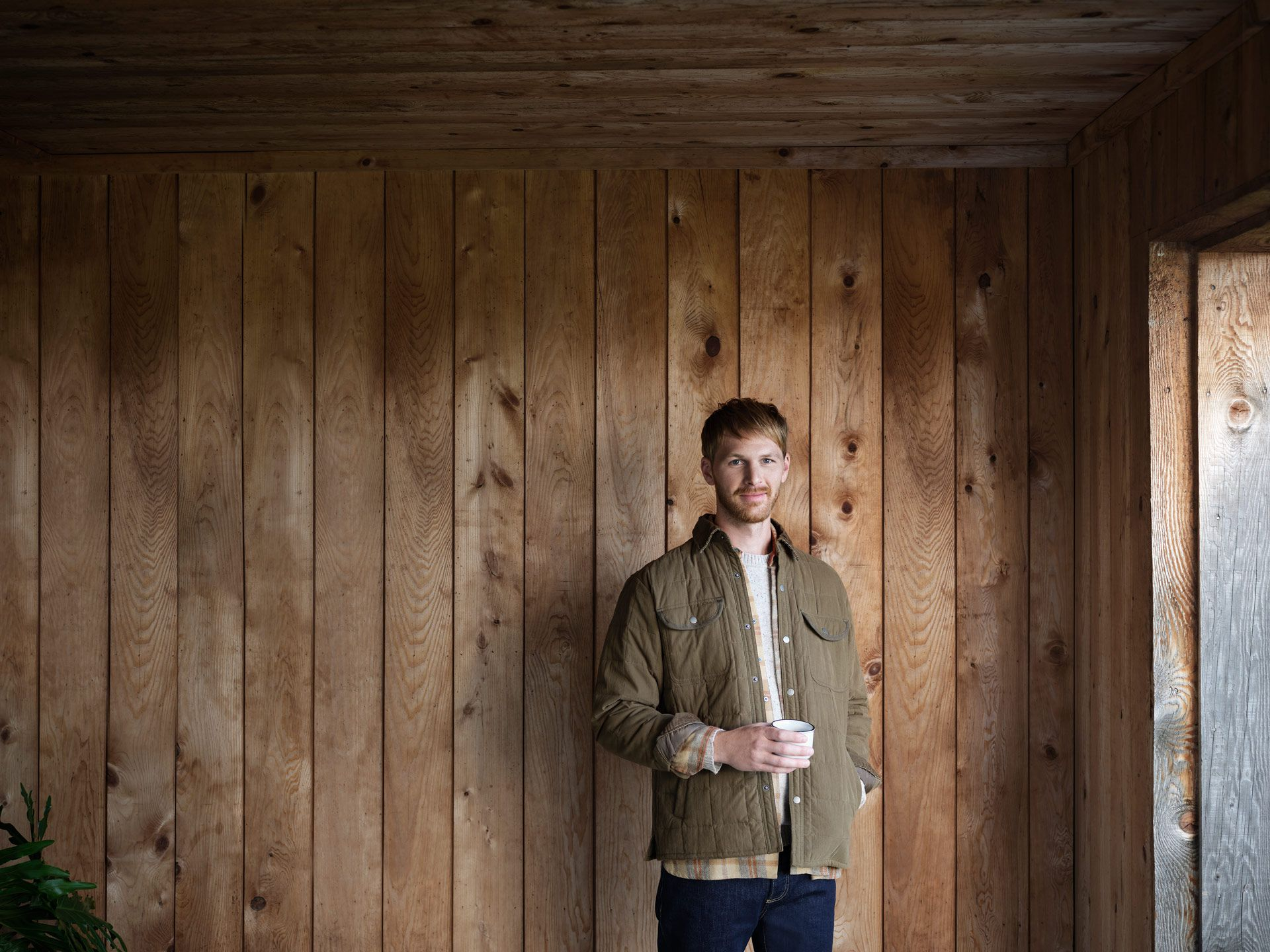 ginger haired man with beard wearing khaki jacket holding white cup in front of wood wall looking at camera photographed by Maxyme G Delisle for Desjardins campaign with Bleu Blanc Rouge