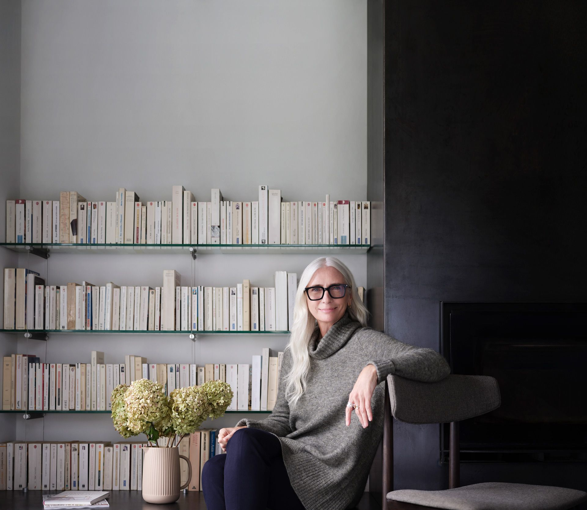 middle aged woman with long white hair sitting on chair in front of her carefully placed library wearing long comfy grey sweater and dark blue leggings smiling looking at camera photographed by Maxyme G Delisle for Desjardins campaign with Bleu Blanc Rouge