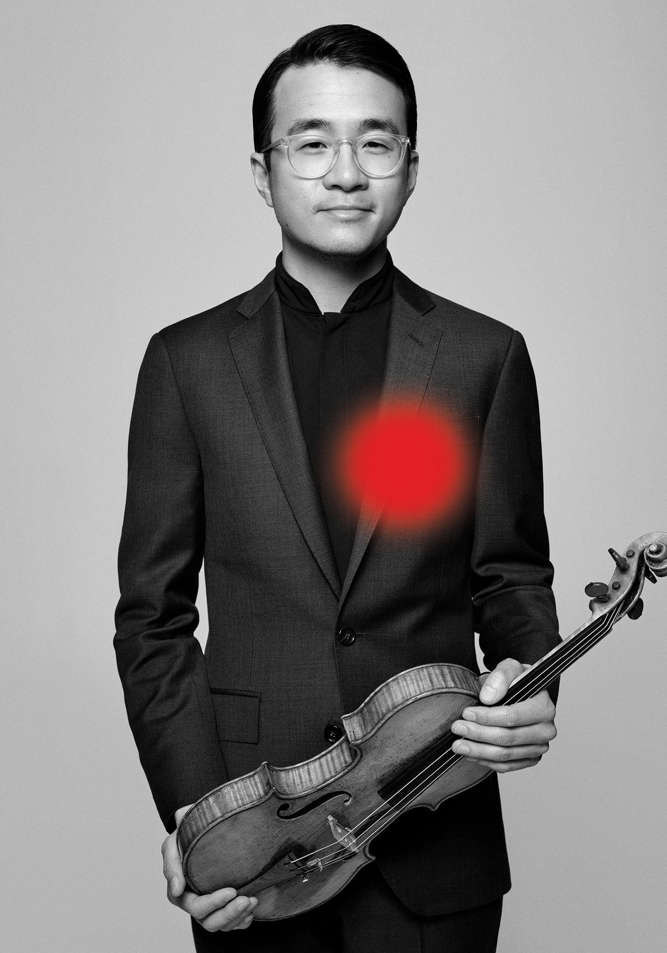 Portrait en noir et blanc d'Andrew Wan tenant son violon, portant des lunettes transparentes et un costume noir.