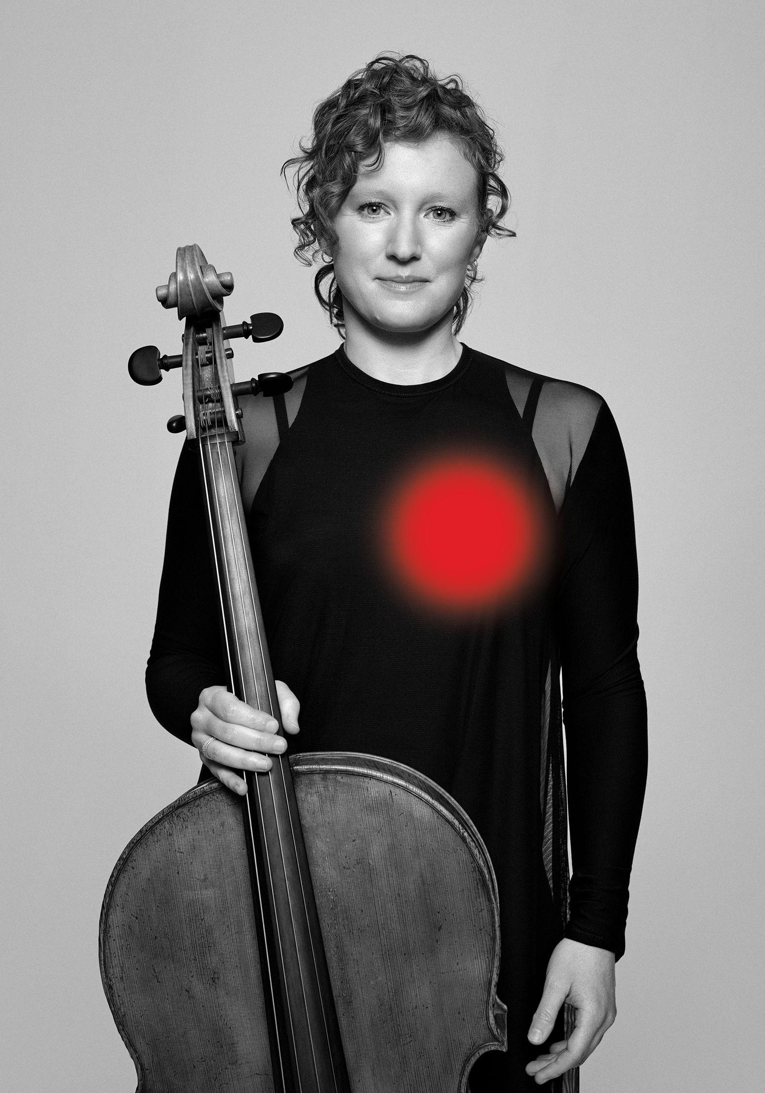 Portrait en noir et blanc d'Anna Burden tenant son violoncelle.