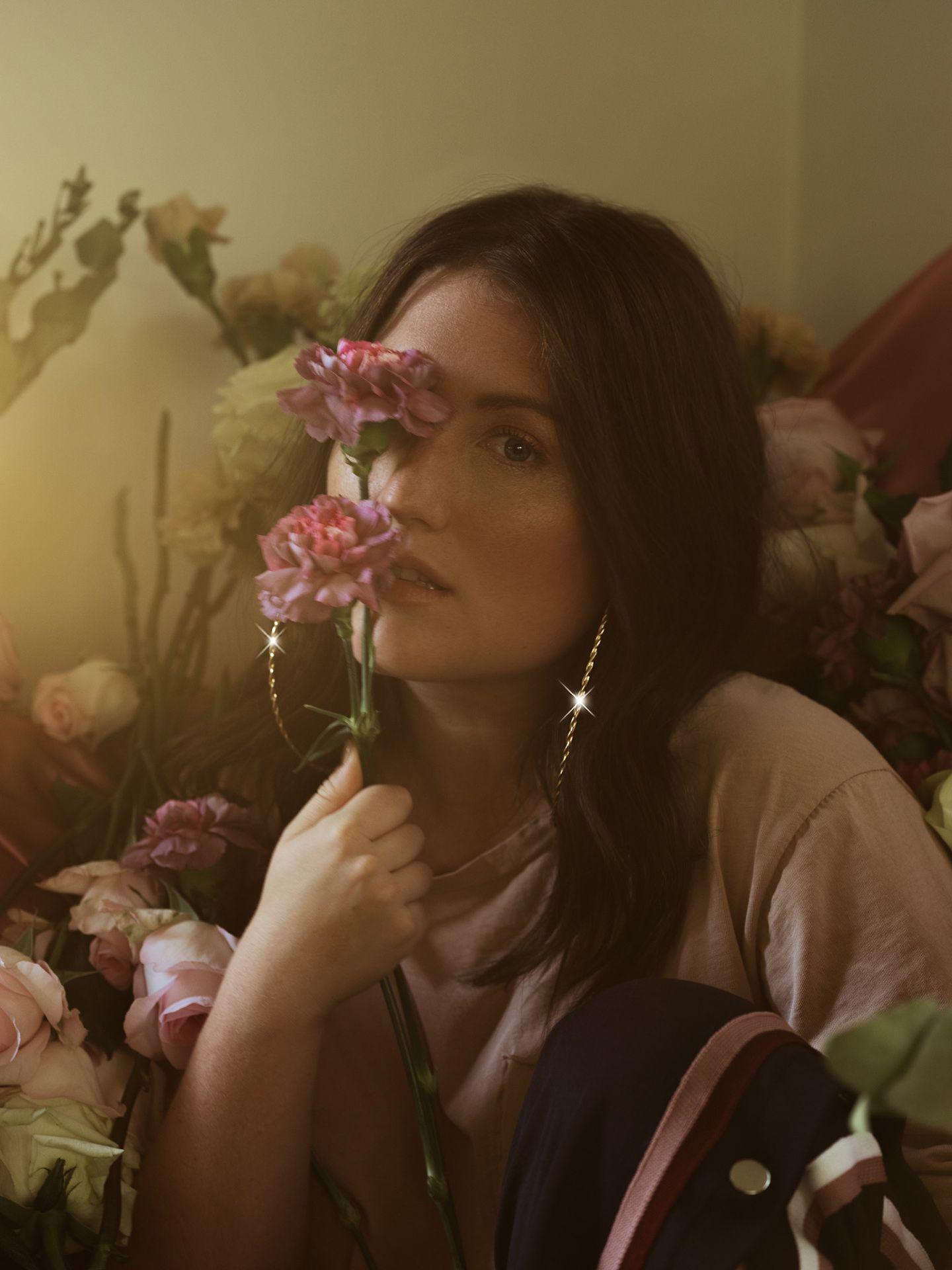 portrait of singer Fanny Bloom half-hidden behind a bouquet of roses for her album Liqueur by Maxyme G. Delisle