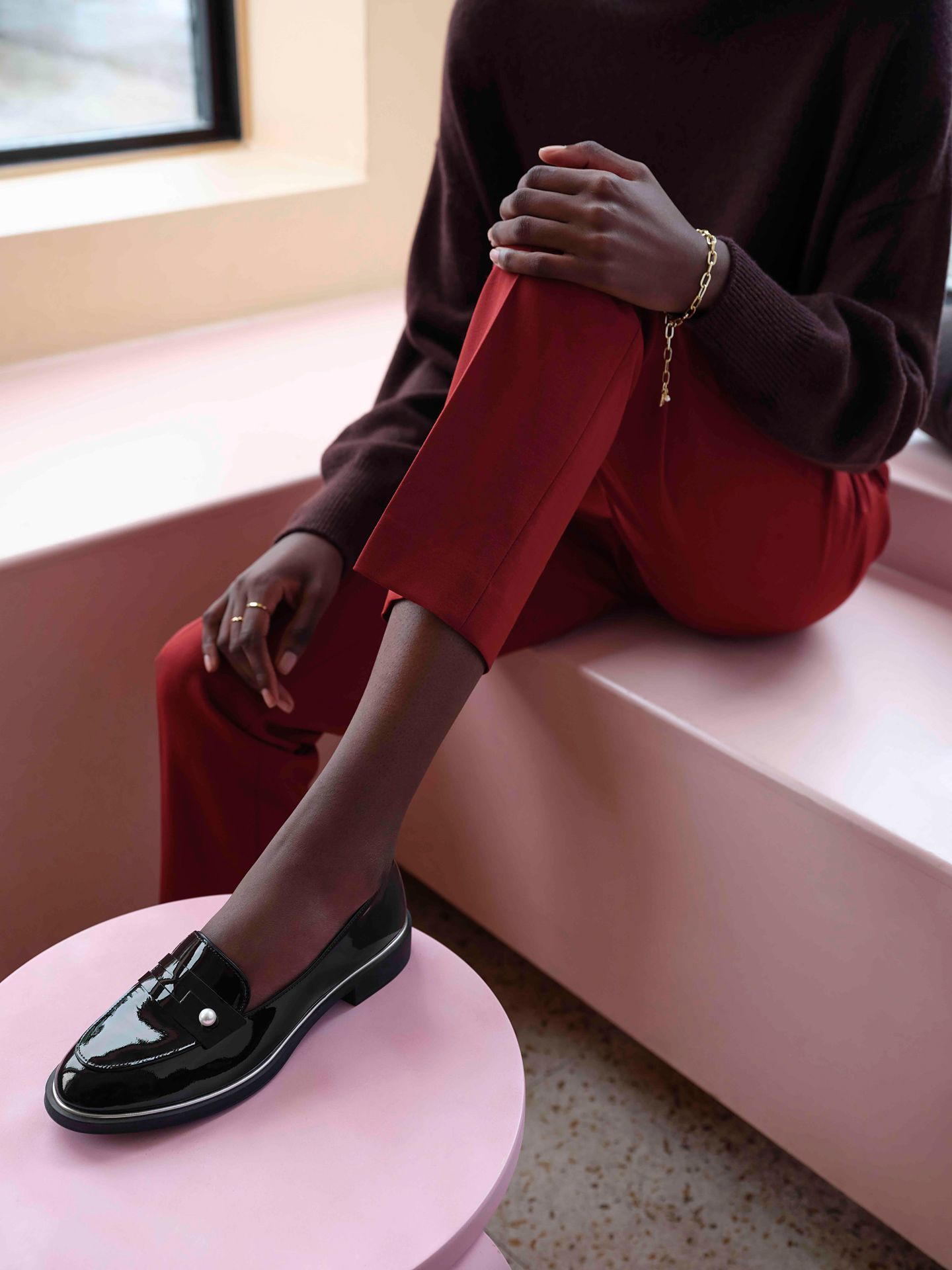 black model wearing red capri pants with oversized dark burgundy sweater and shiny black loafers by Maxyme G Delisle with artistic direction from Studio TB at Pastel Rita for Jean-Paul Fortin Fall collection