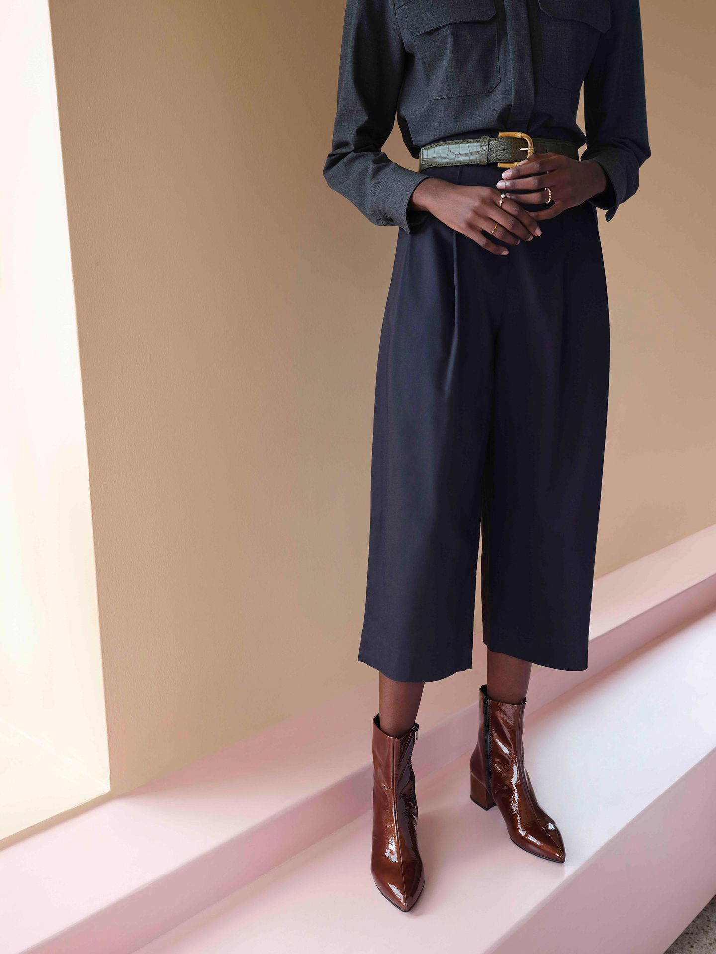 black model wearing large dark blue pants with dark blue shirt and shiny brown high-heeled boots posing on pink ground by Maxyme G Delisle with artistic direction from Studio TB at Pastel Rita for Jean-Paul Fortin Fall collection
