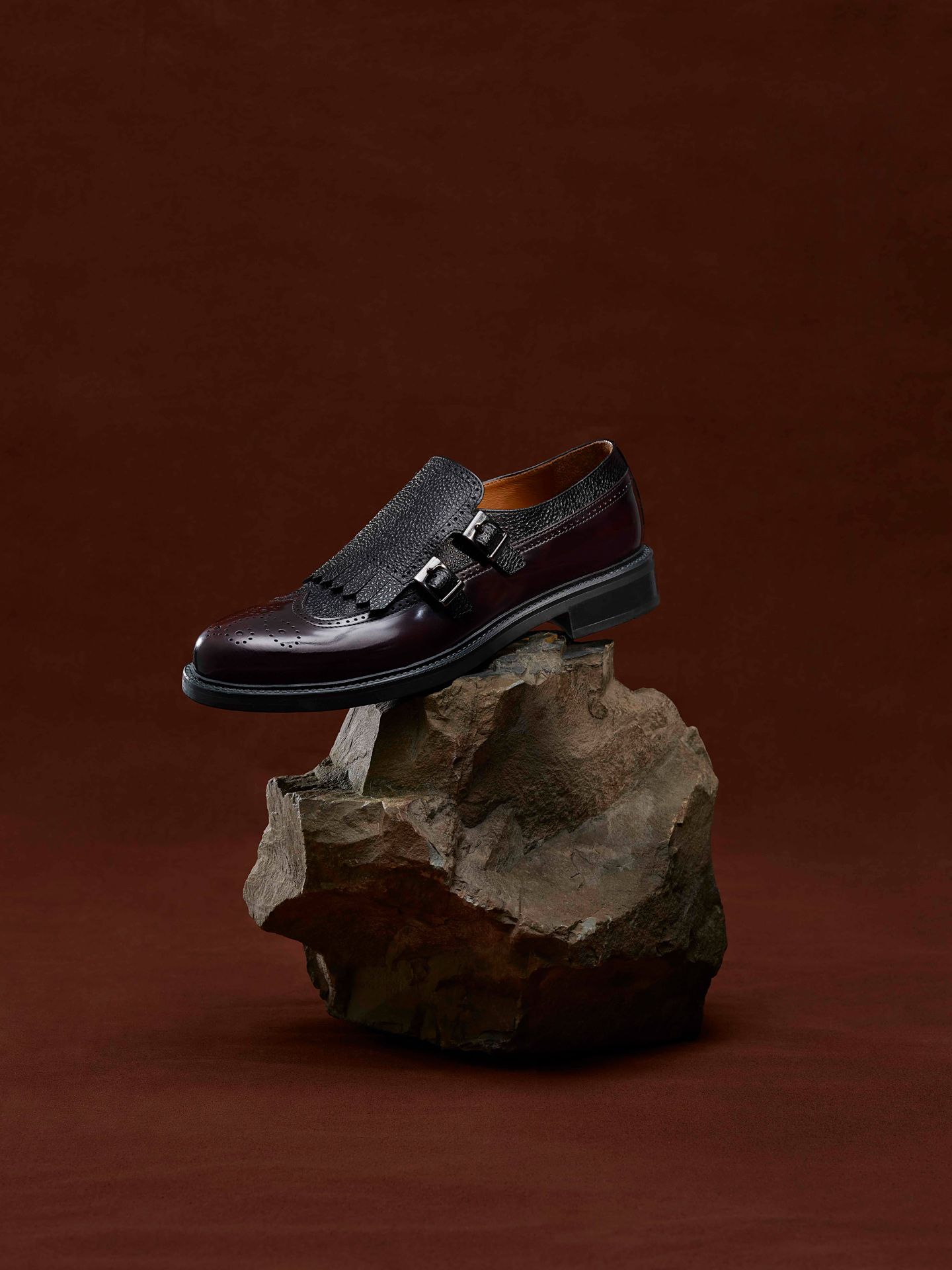 black leather shoe on brown rock on dark red background photographed by Maxyme G Delisle with artistic direction from Studio TB for Jean-Paul Fortin Fall collection