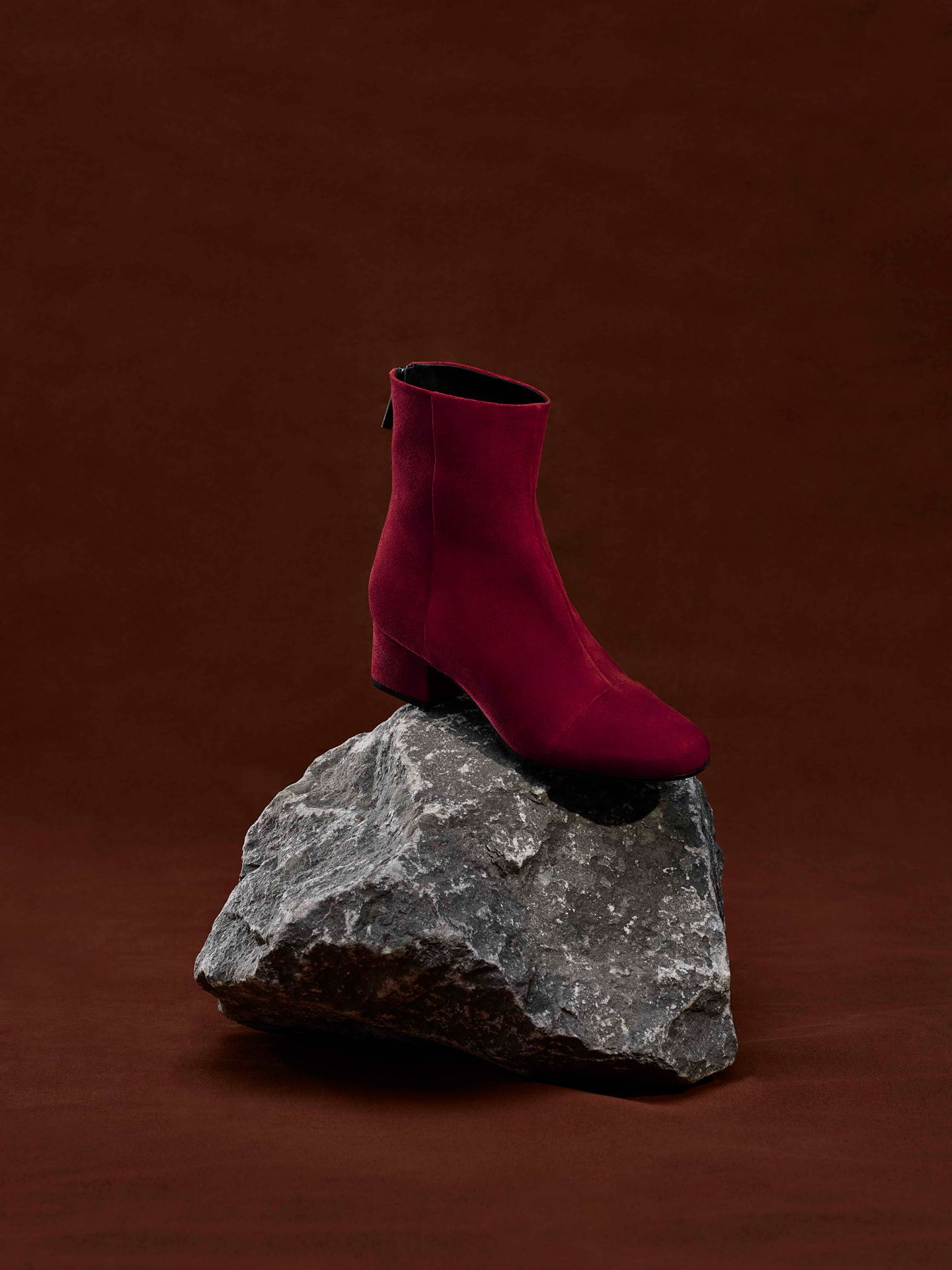 red suede boot on grey rock over red-brown background by Maxyme G Delisle with artistic direction from Studio TB for Jean-Paul Fortin Fall collection